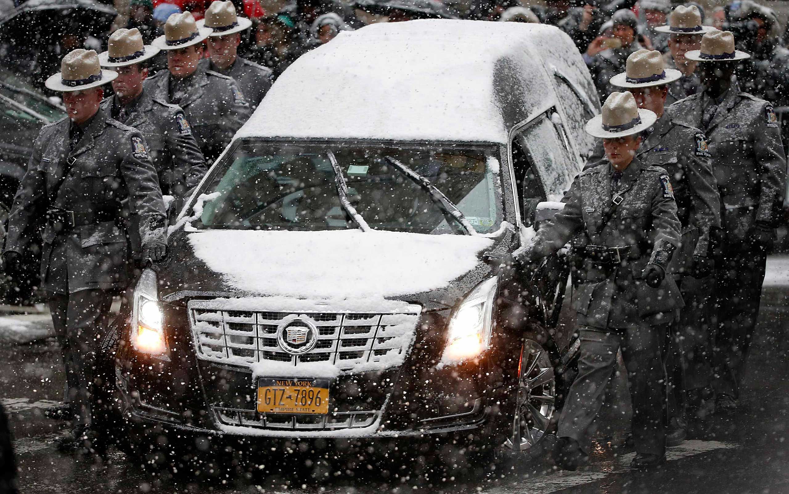 The hearse carrying the casket of former New York Governor Mario Cuomo is escorted by members of the New York State Police as it arrives at St. Ignatius Loyola Church for funeral service in New York on Jan. 6, 2015.