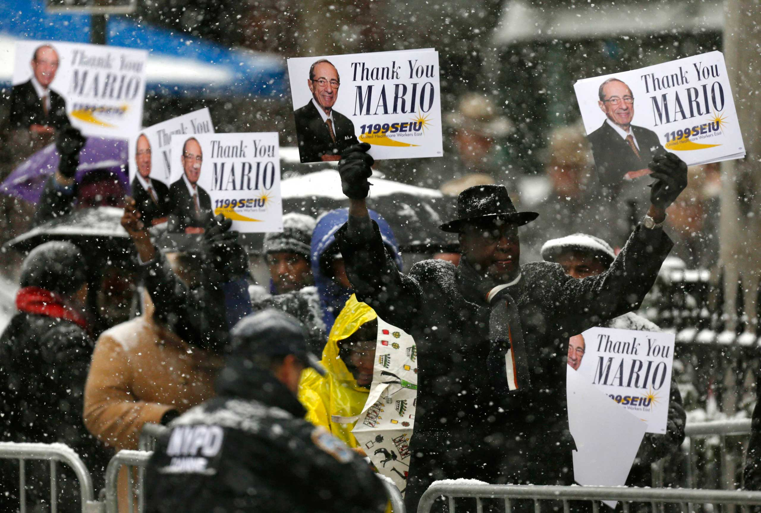 People holds signs outside St. Ignatius Loyola Church,before the funeral service for former New York Governor Mario Cuomo in New York on Jan. 6, 2015.