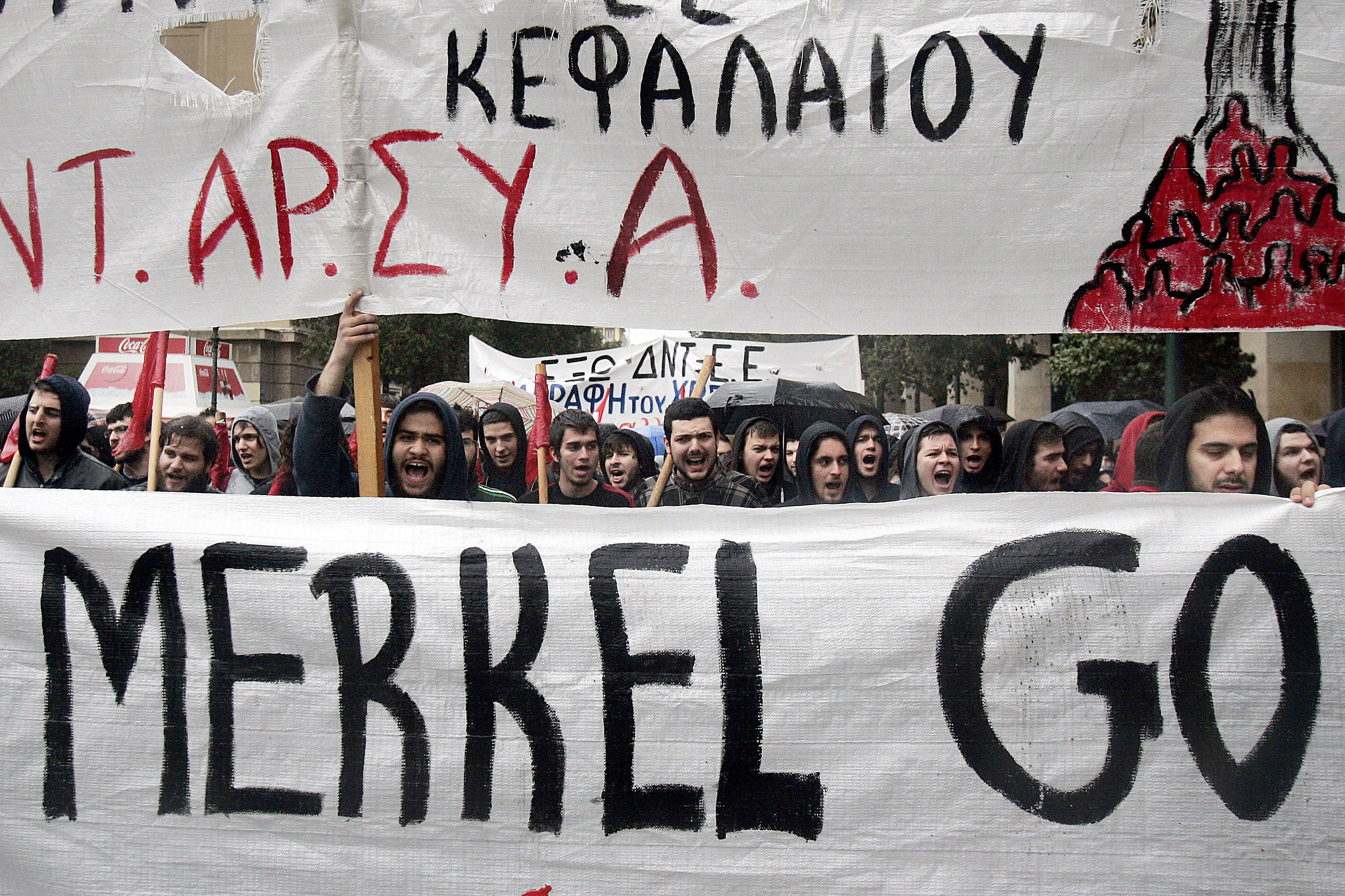 Protesters hold a banner as they march during a demonstration against the visit of Germany's Chancellor Angela Merkel on April 11, 2014 in Athens.
