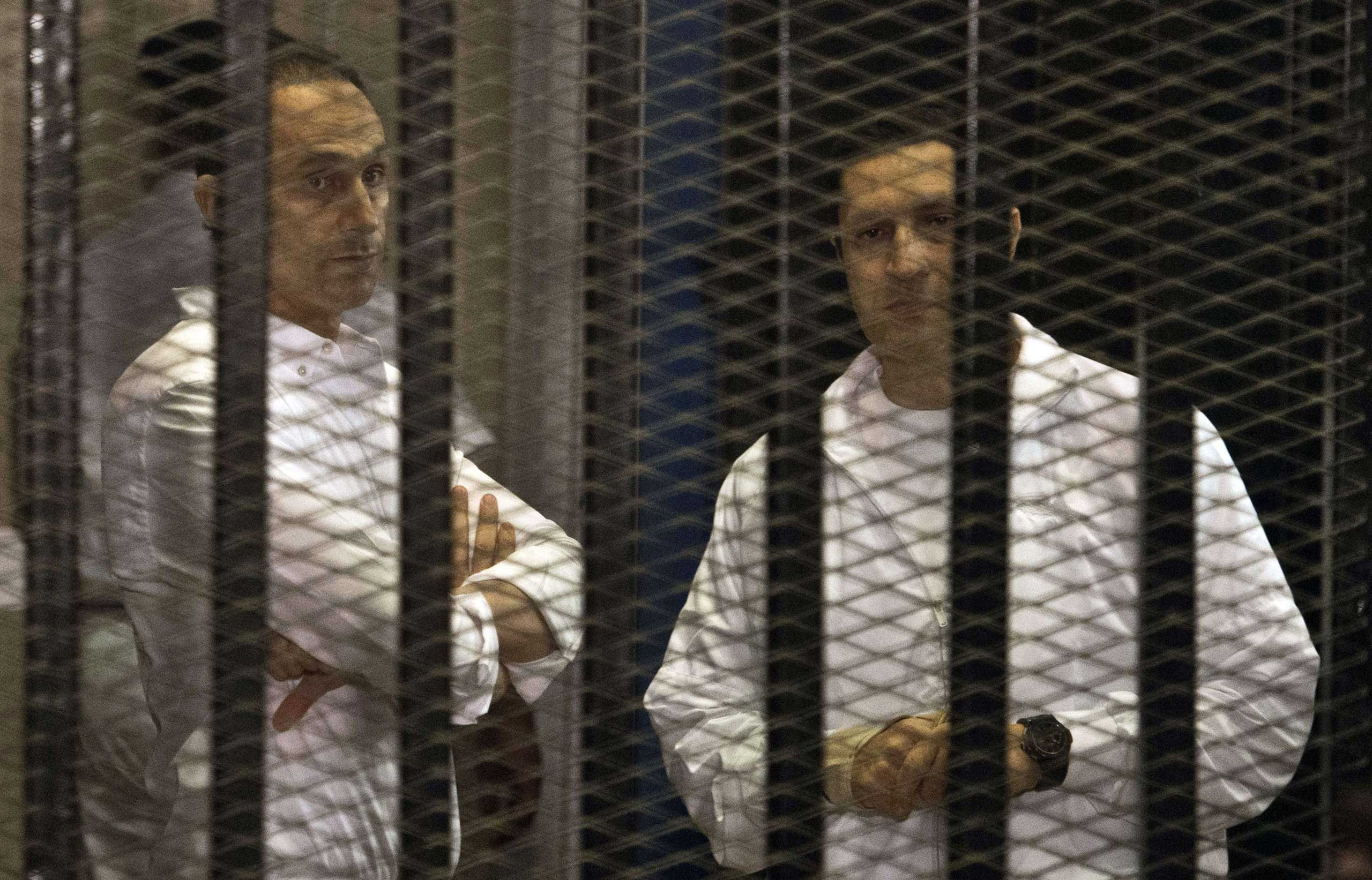 The sons of ousted Egyptian president Hosni Mubarak, Gamal and Alaa  behind the defendants' cage during their retrial at the Police Academy in Cairo in 2013.