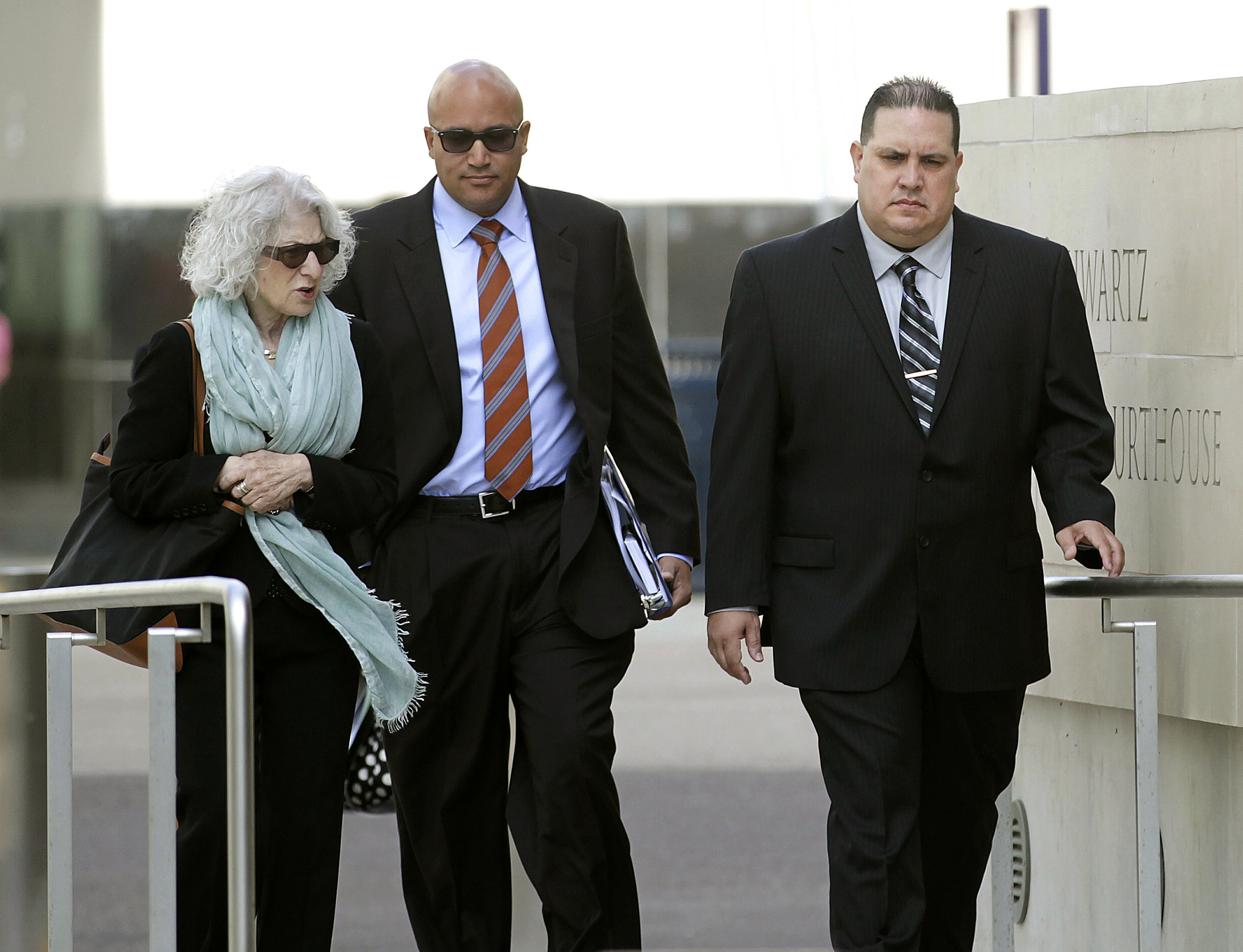 In this photo taken on Nov. 20, 2013, Navy Cmdr. Jose Luis Sanchez, right, walks with unidentified individuals in San Diego, Calif.