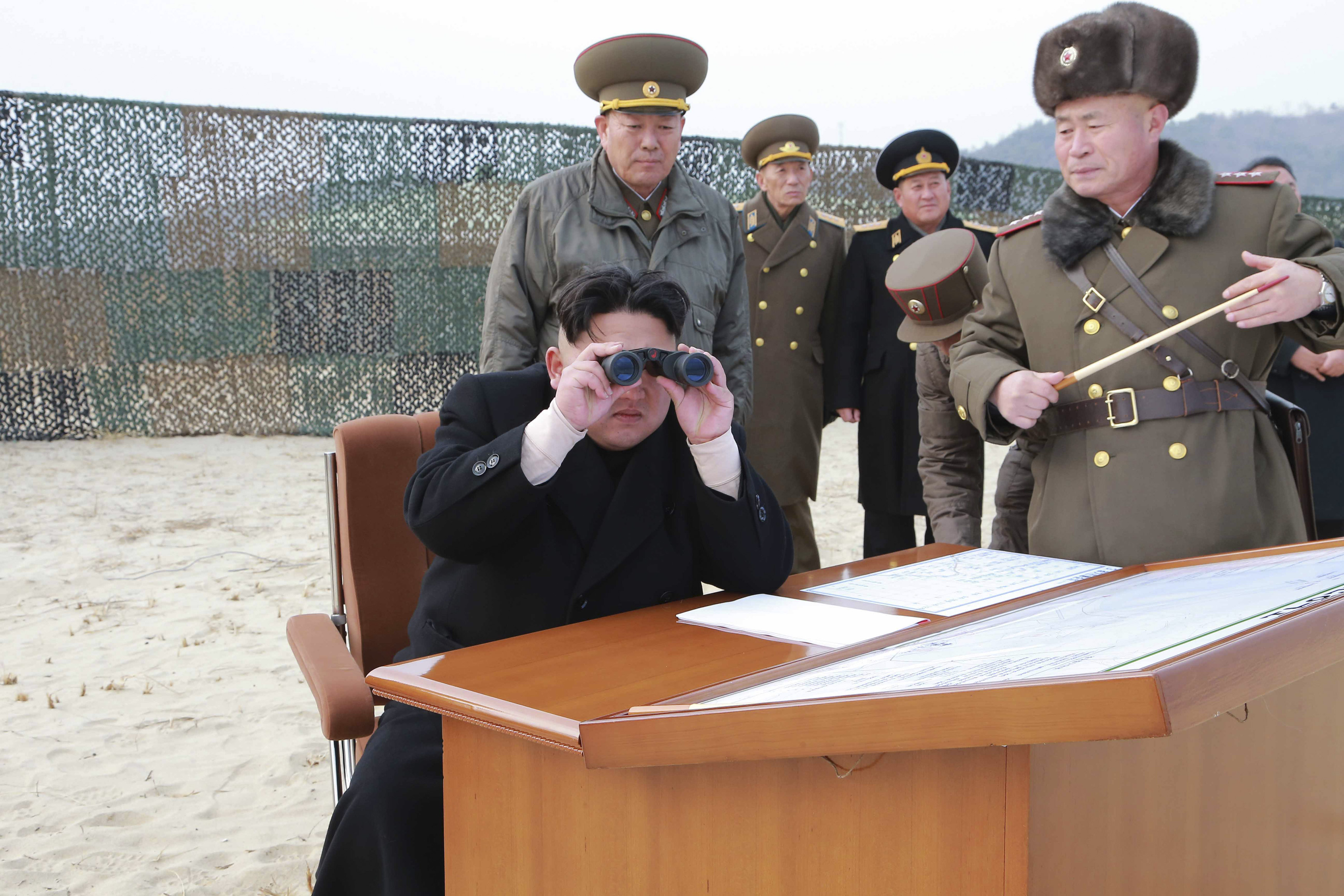 North Korean leader Kim Jong Un looks through a pair of binoculars as he guides the multiple-rocket launching drill of women's sub-units under KPA Unit 851, in Pyongyang in this undated photo released on Dec. 30, 2014.