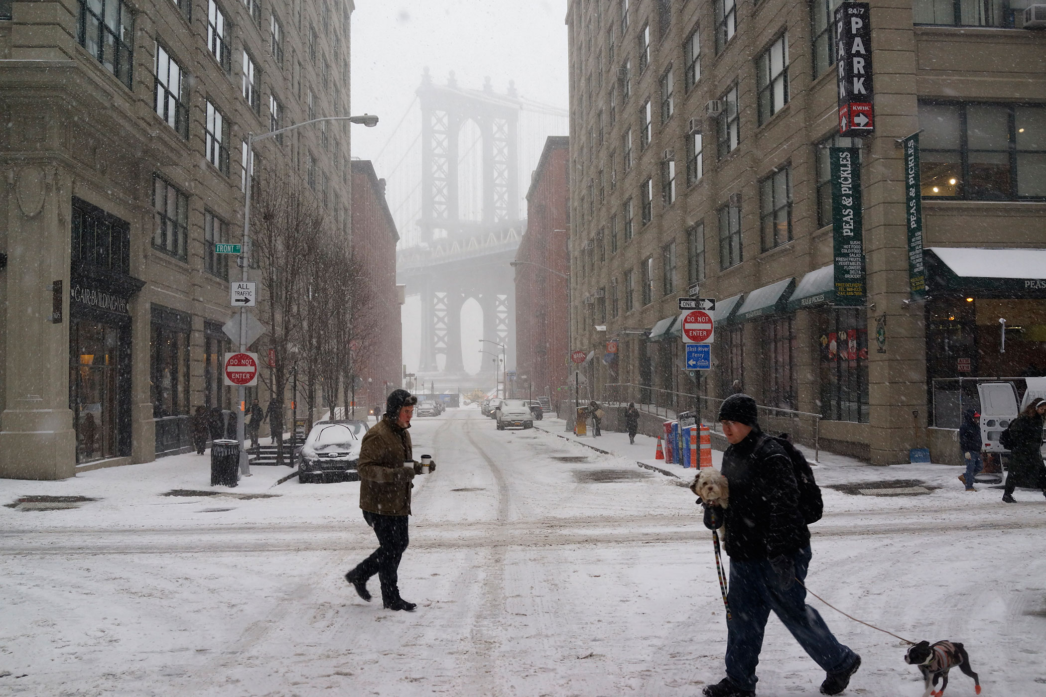 People walk in front of the Manhattan Bridge in the DUMBO neighborhood as it snows in Brooklyn, NY on Jan. 26, 2015