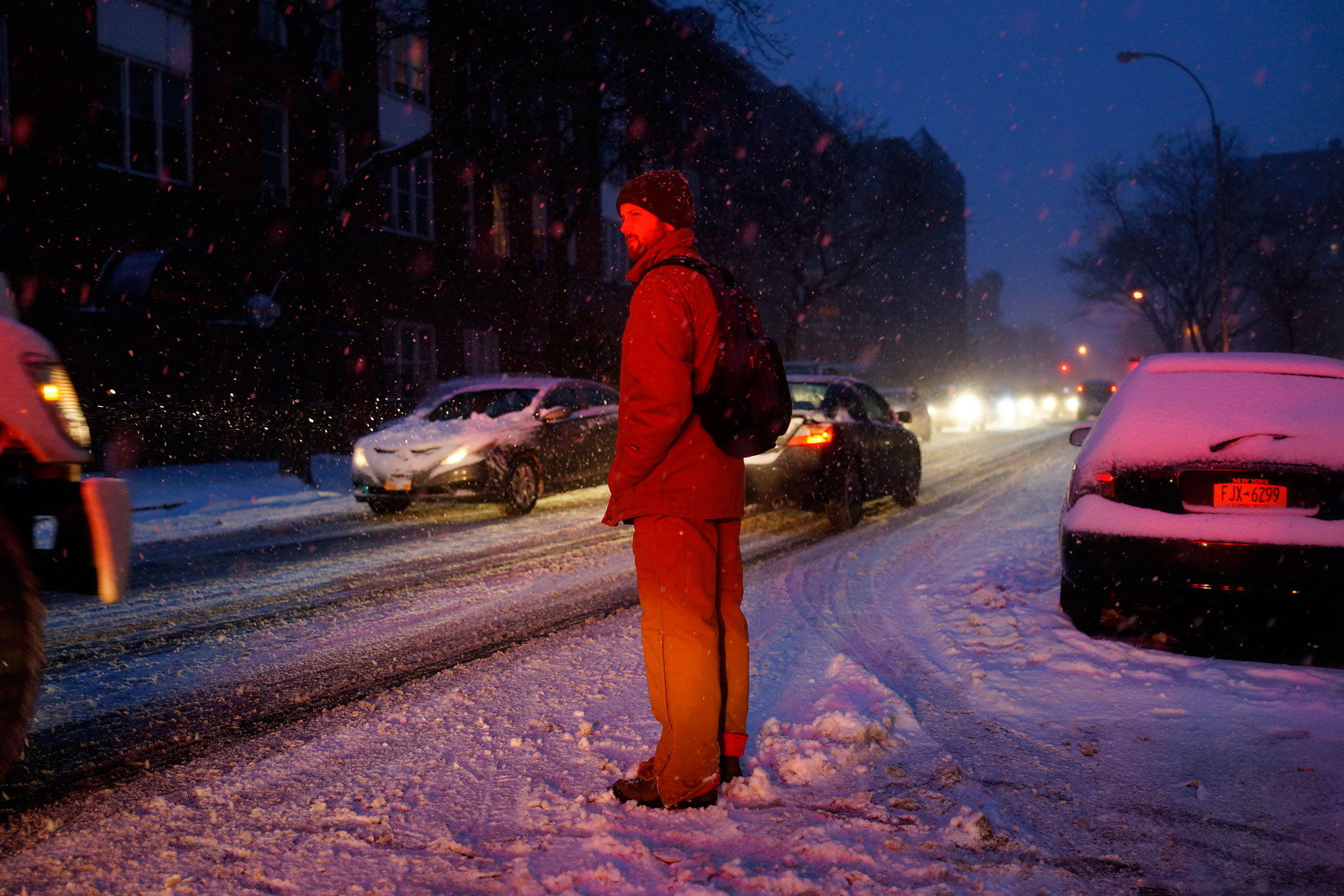 A man waits to cross the street in Brooklyn, NY on Jan. 26, 2015.