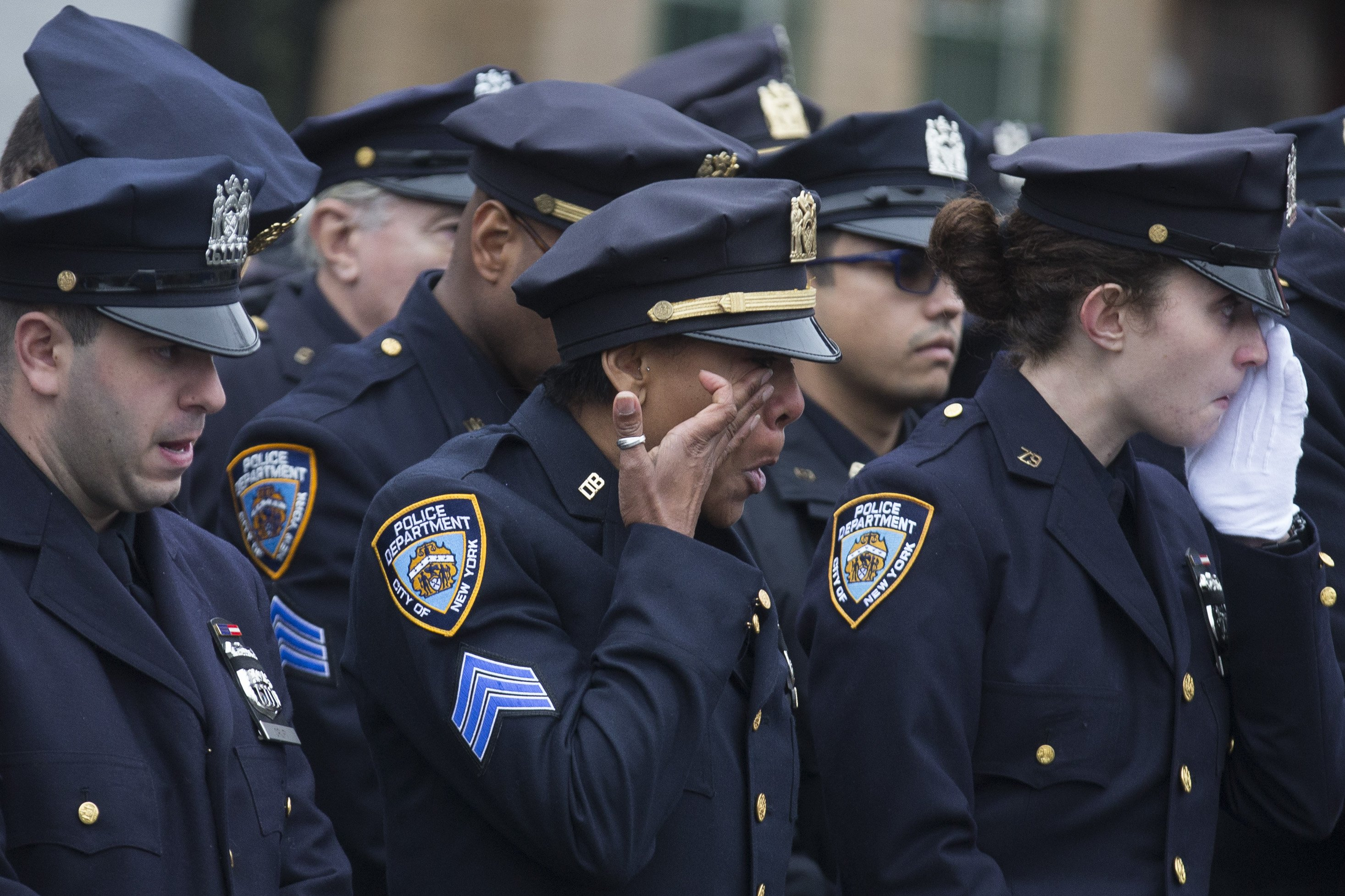 Police officers wipe their tears during the funeral of New York Police Department Officer Wenjian Liu at Aievoli Funeral Home Jan. 4, 2015 in the Brooklyn borough of New York.