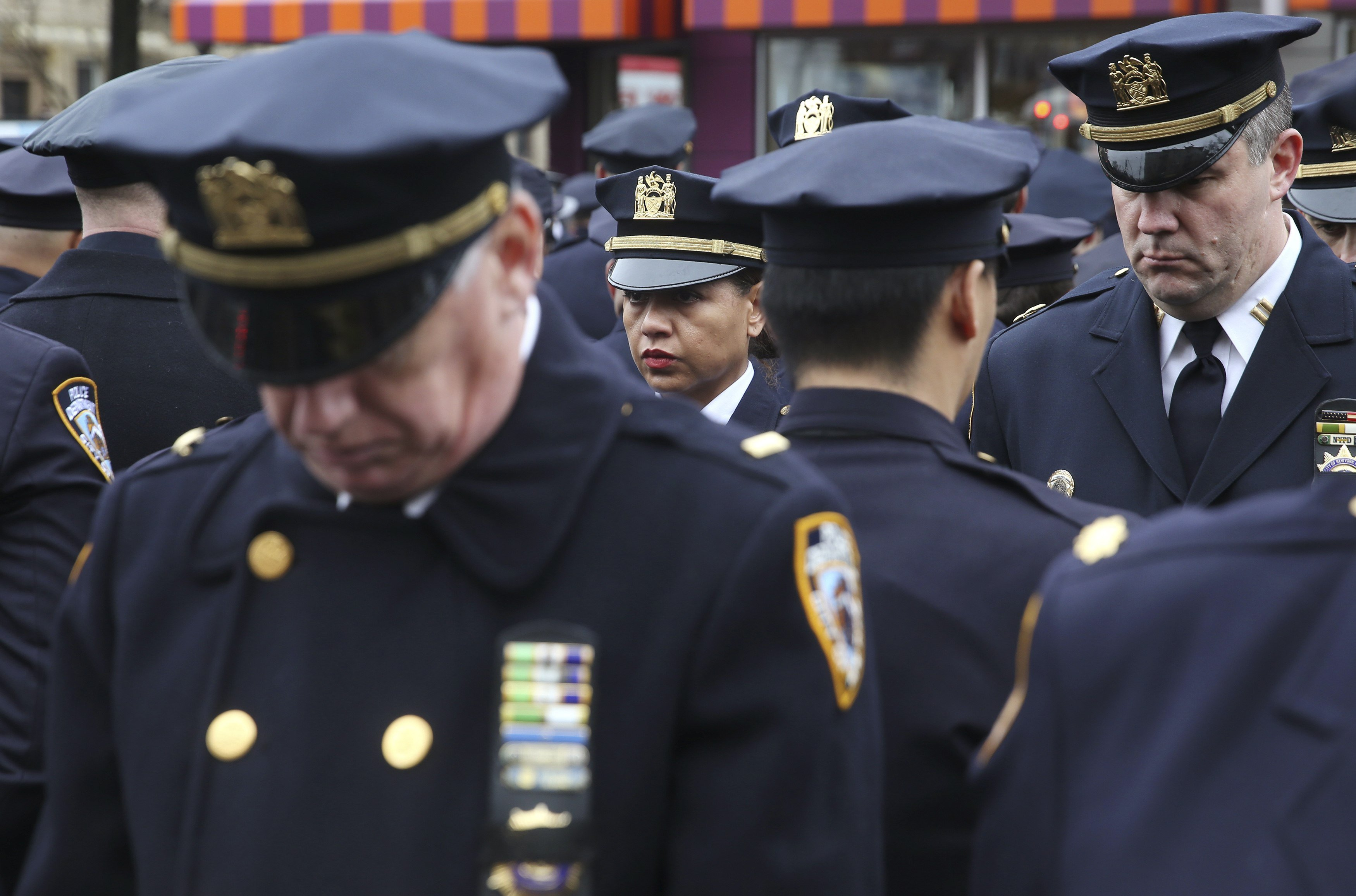 Law enforcement officers stand with some turning their backs as New York City Mayor Bill de Blasio speaks on a monitor outside the funeral for NYPD officer Wenjian Liu in the Brooklyn borough of New York on Jan. 4, 2015.
