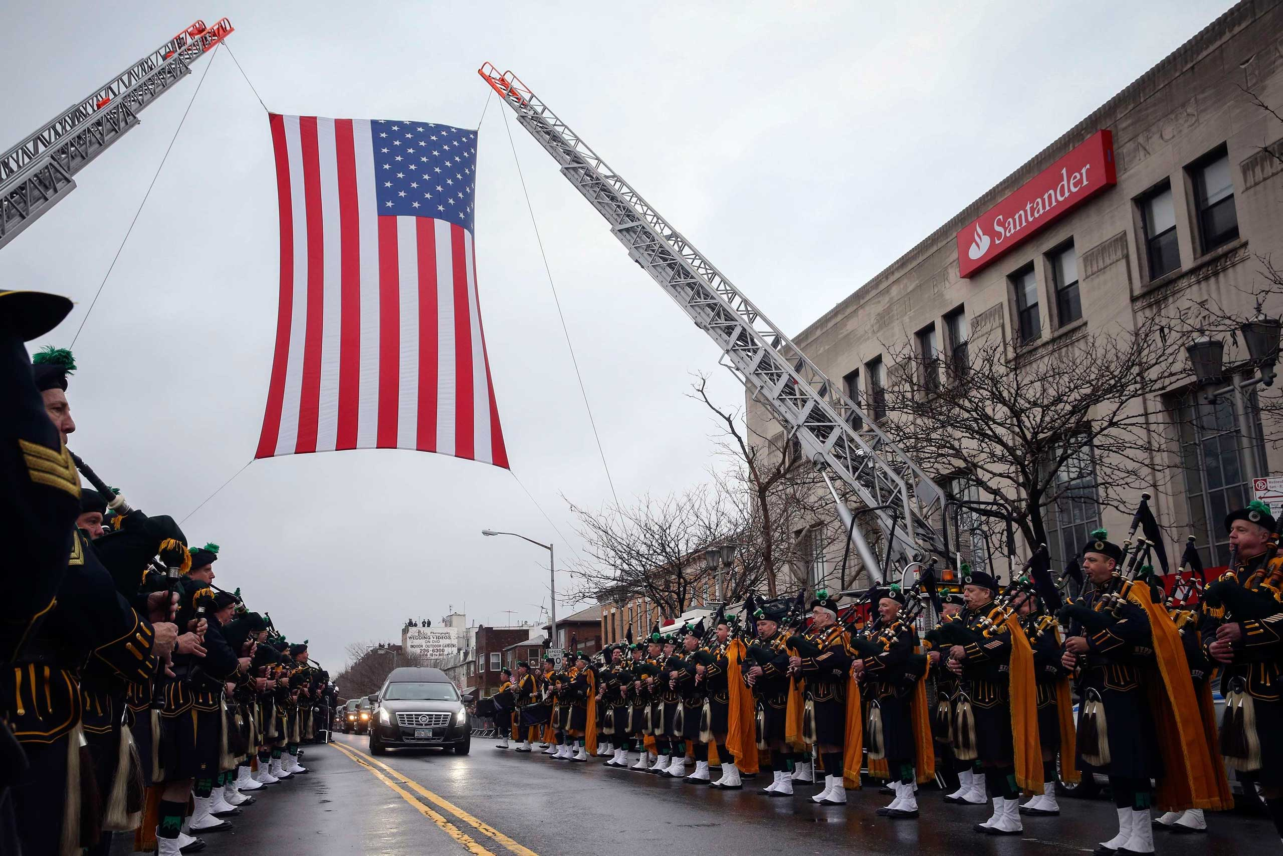 The hearse carrying NYPD officer Wenjian Liu makes its way under a US flag en route to the cemetery in the Brooklyn borough of New York on Jan. 4, 2015.
