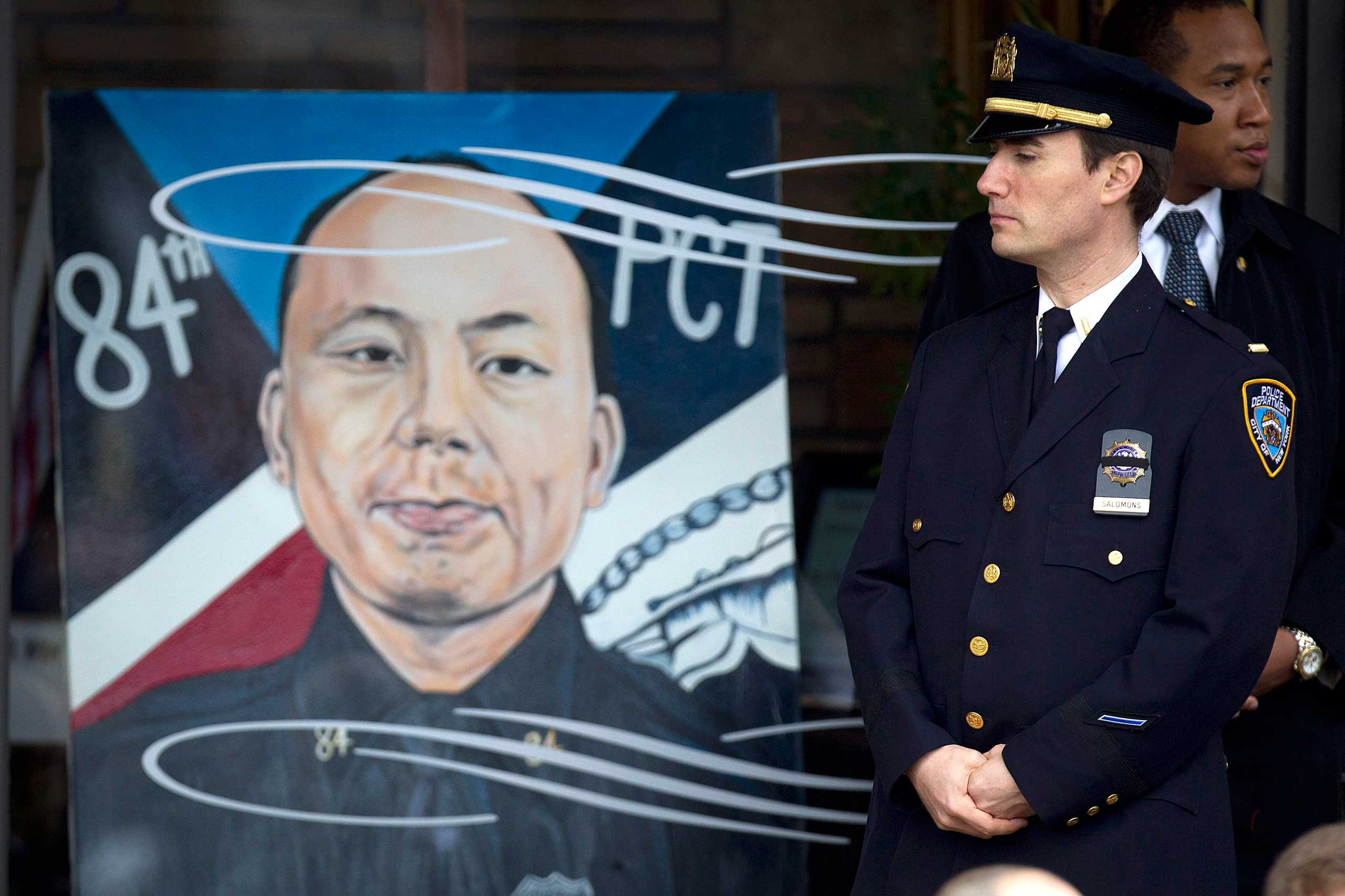A policeman stands next to an image of slain New York Police Department officer Wenjian Liu during his funeral in the Brooklyn borough of New York on Jan. 4, 2015.