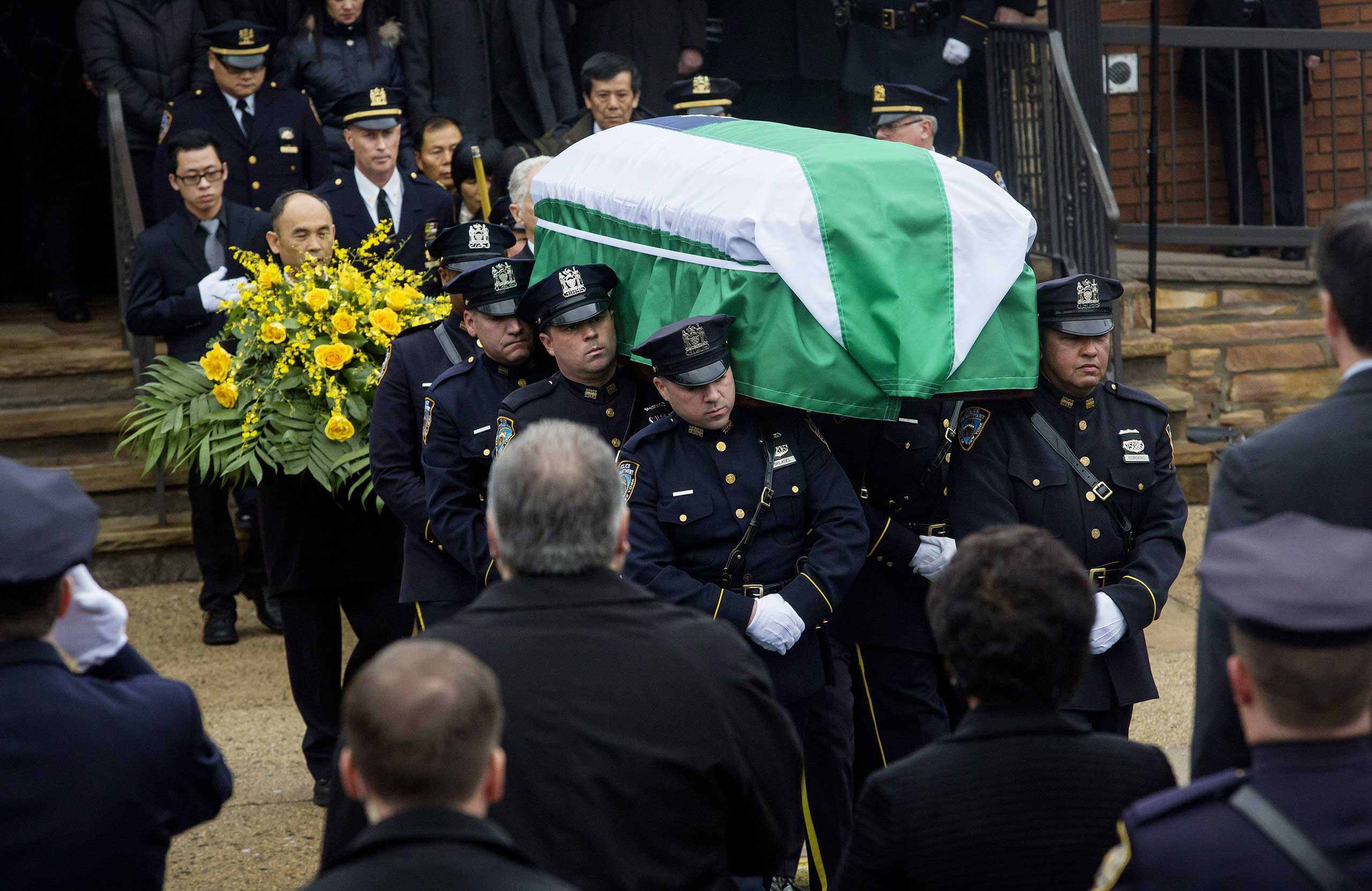Officers carry the casket of Police Officer Wenjian Liu from a funeral service at on Jan. 4, 2015 in the Brooklyn borough of New York.