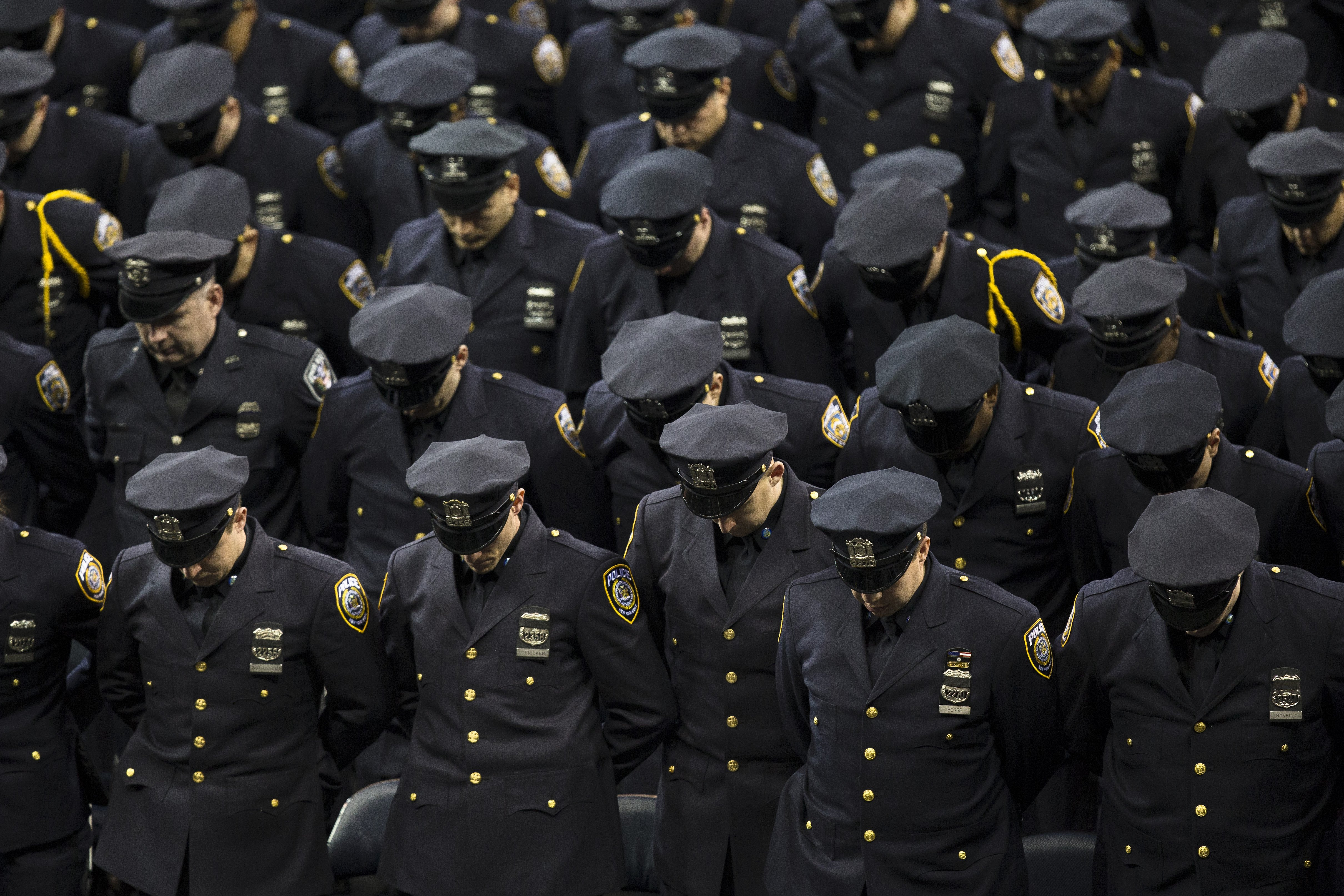 New recruits bow their heads for a moment of silence during a New York Police Academy graduation ceremony at Madison Square Garden in New York City on Dec. 29, 2014.