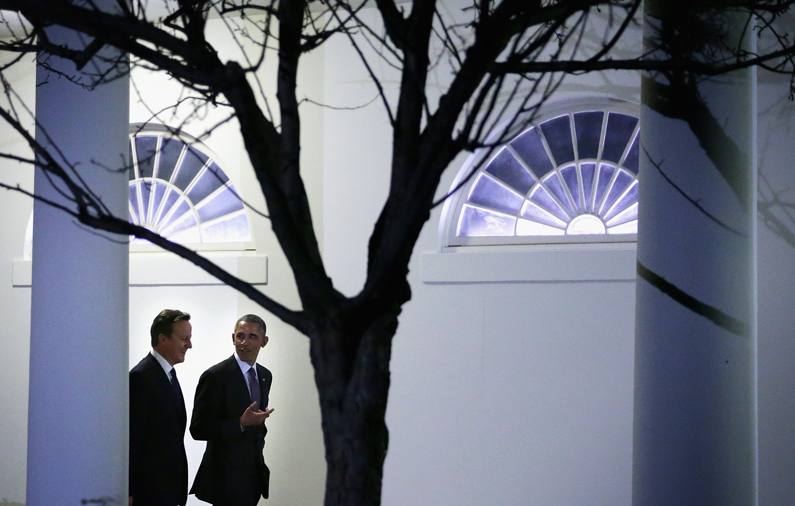 U.S. President Barack Obama (R) walks with British Prime Minister David Cameron (L) through the colonnade as they are on their way for a working dinner at the Blue Room of the White House January 15, 2015 in Washington, DC. Prime Minister Cameron is on a two-day visit to Washington.