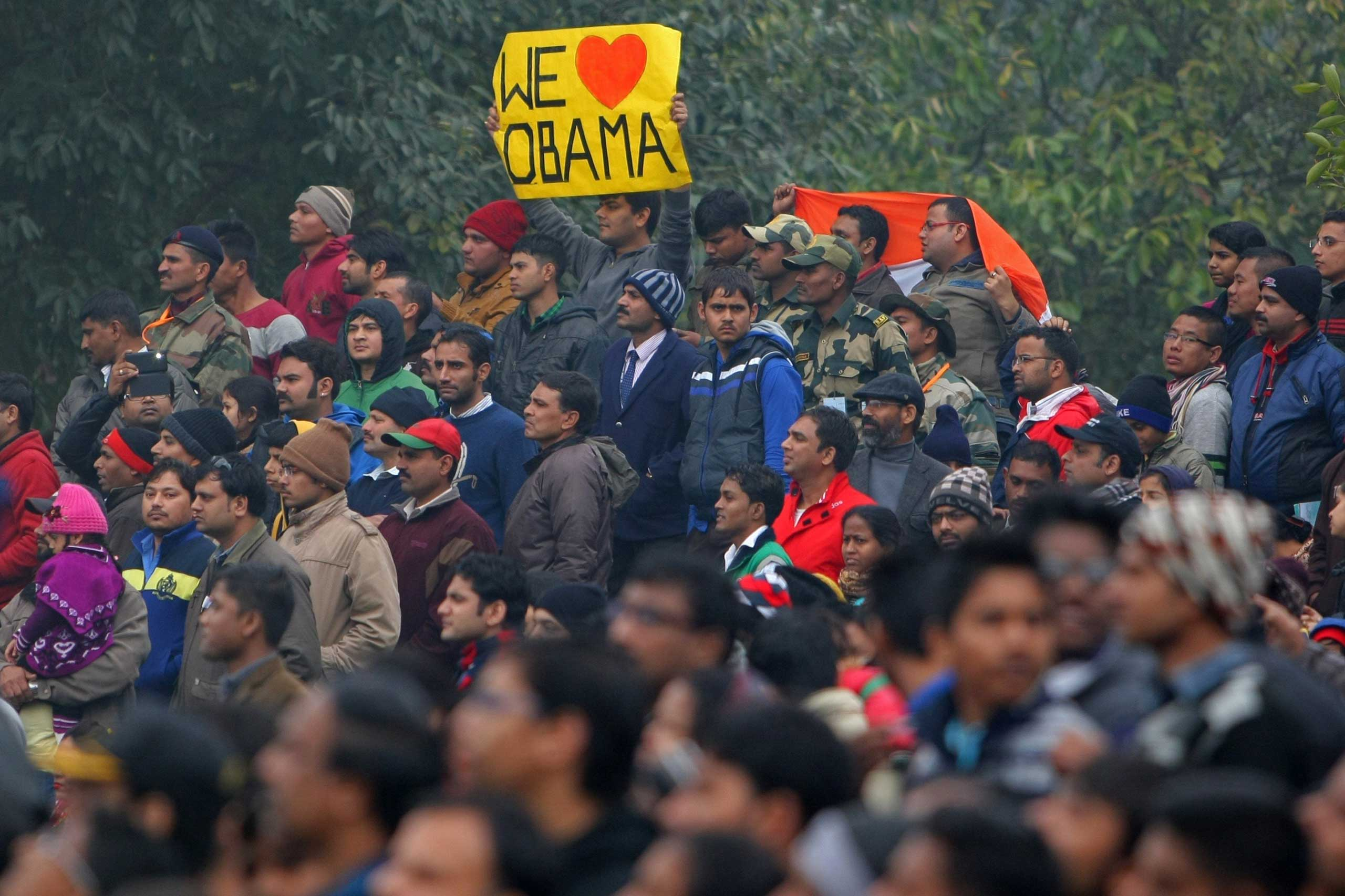 """A spectator holds a placard that reads """"We Love Obama"""" as the motorcade of President Obama departs following the conclusion of the country's Republic Day Parade in New Delhi on Jan. 26, 2015."""