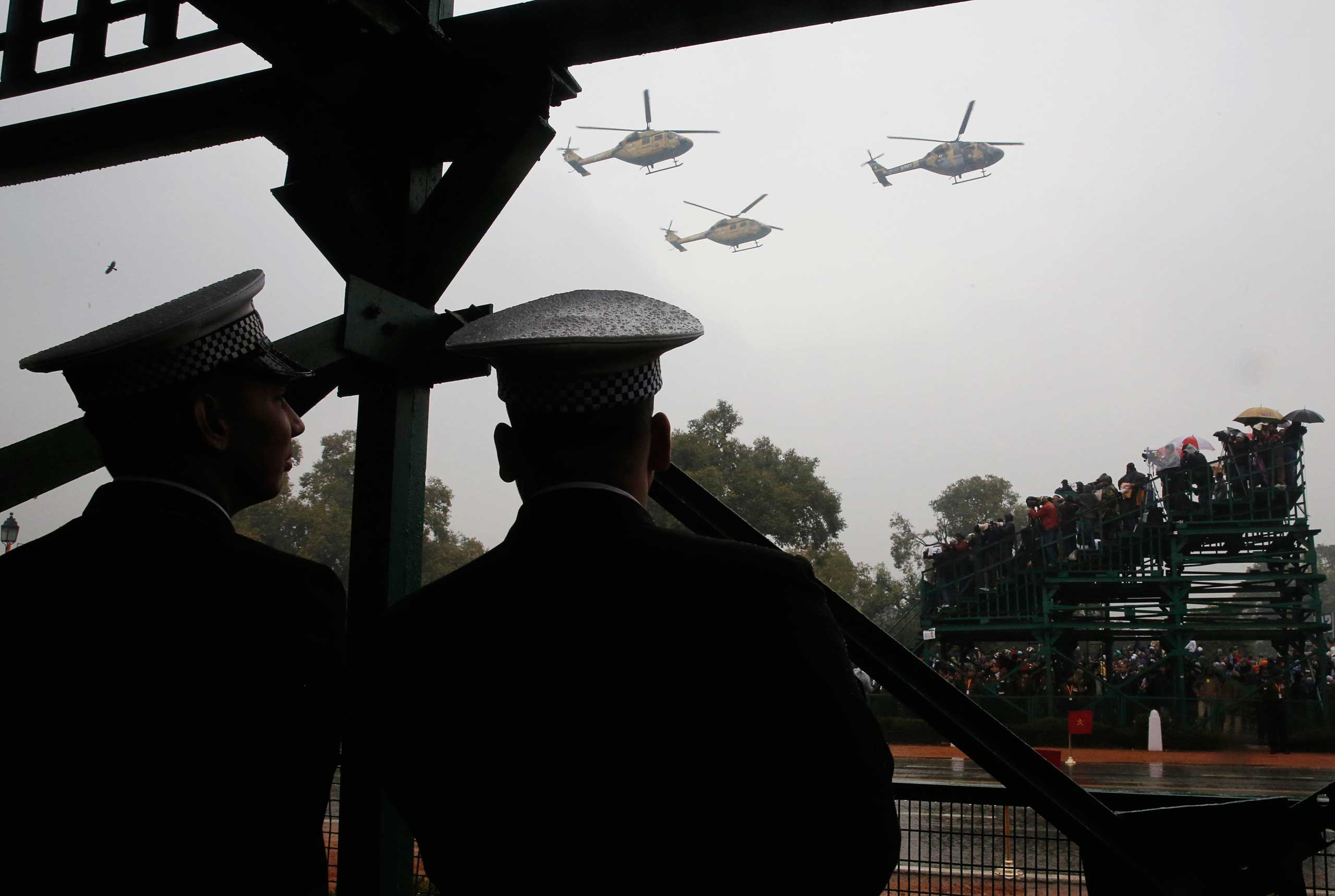 Navy sailors watch military helicopters fly-by during India's Republic Day parade in New Delhi, Jan. 26, 2015.