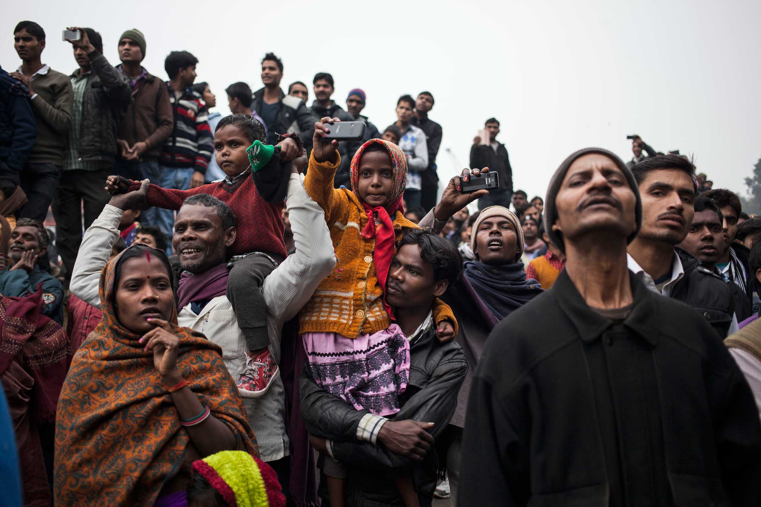 A girl sits on the shoulder of a man and holds up a mobile phone as the Republic Day parade marches past in the old parts of New Delhi, Jan. 26, 2015.