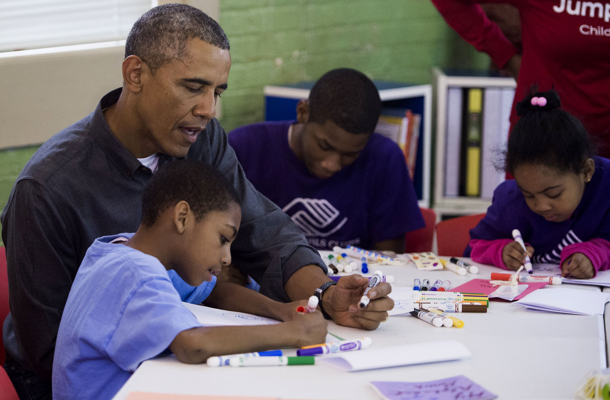 President Barack Obama sits alongside children as he participates in a literacy project at the Boys and Girls Club of Greater Washington in honor of Martin Luther King, Jr. Day in Washington, DC, Jan. 19, 2015.