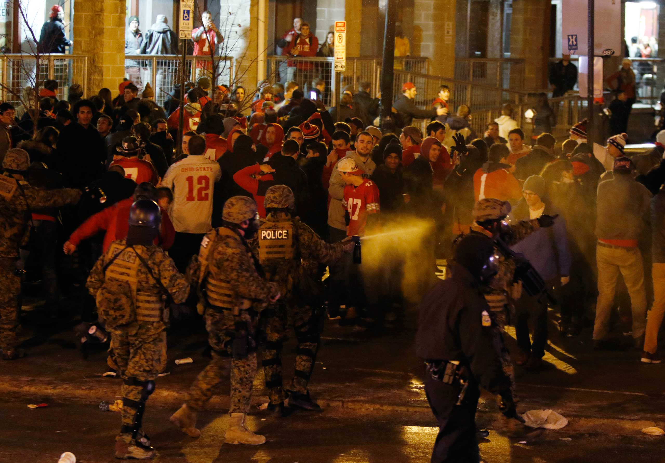 Police officers try to disperse the crowd of Ohio State fans trying to block High Street in Columbus, Ohio, as they celebrate the Buckeye's 42-20 win over Oregon following the National Championship football game between Ohio State and Oregon, Jan. 12, 2015.