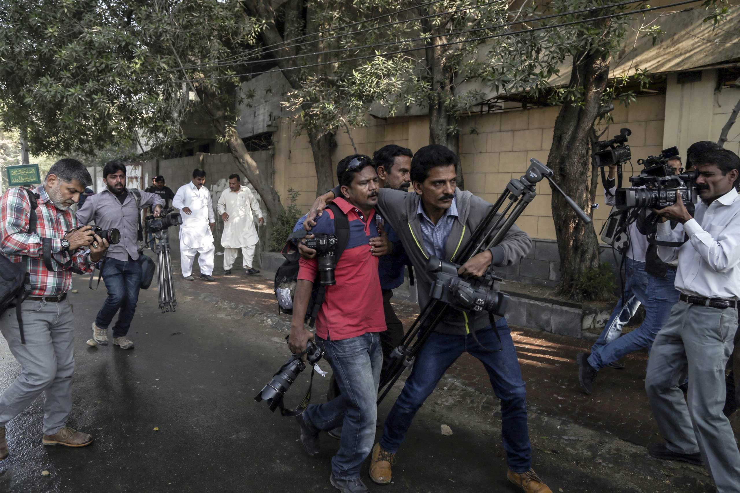 Pakistani journalists help a colleague who was injured in clashes between police and the supporters of Islamic political party Jamat-e-Islami during a protest against the French magzine 'Charlie Hebdo' for publishing the caricatures of the prophet Muhammad, in Karachi, Pakistan on Jan. 16, 2015.