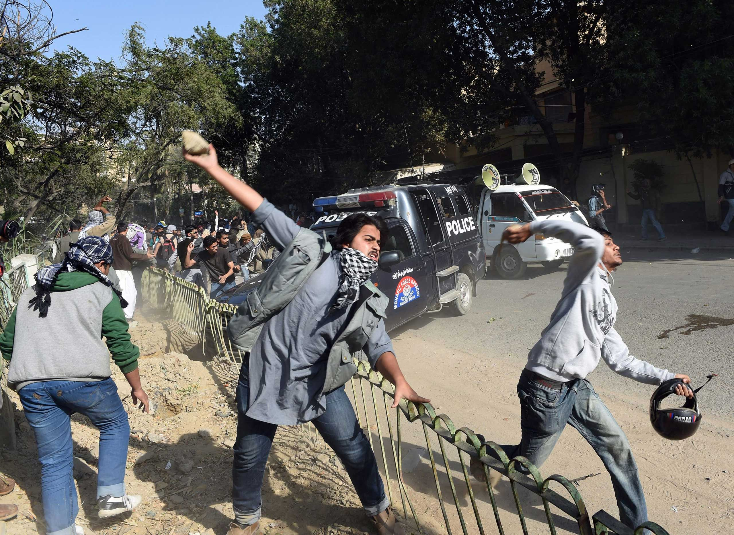 Pakistani activists of the Jamaat-e-Islami religious party throw stones toward riot police during a protest against the printing of satirical sketches of the Prophet Muhammad by French magazine Charlie Hebdo in Karachi, Pakistan on Jan.16, 2015.