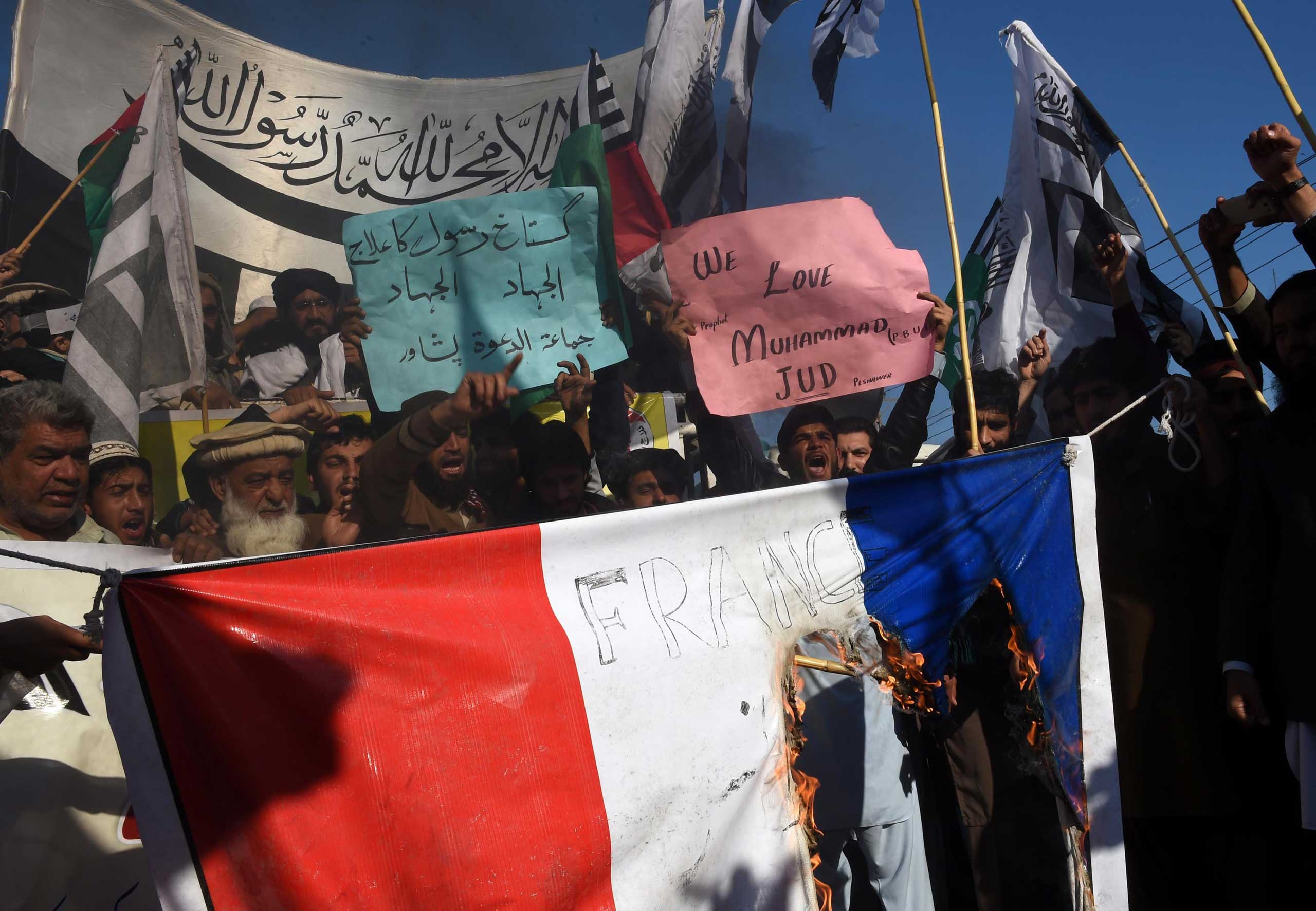Pakistani protesters burn a French flag during a protest against the printing of satirical sketches of the Prophet Muhammad by French magazine Charlie Hebdo in Peshawar, Pakistan on Jan. 16, 2015.