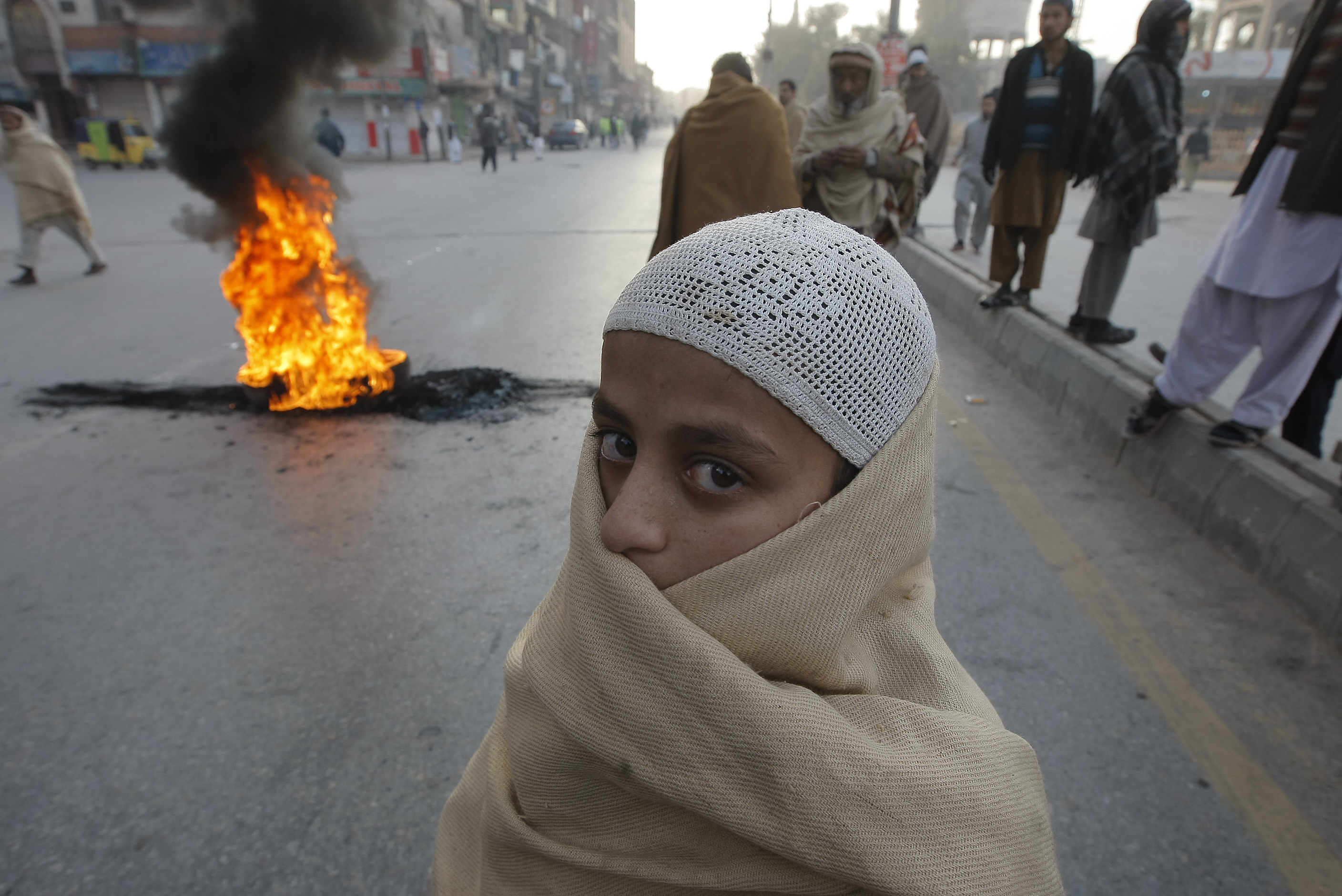 A Pakistani religious student stands before a tire set on fire by anti-government protesters, Wednesday, Dec. 31, 2014 in Peshawar, Pakistan. Police have arrested demonstrators demanding the government to unmask culprits of the Taliban attack on a military run school where scores of children were killed on Dec. 16, 2014. (AP Photo/Mohammad Sajjad)