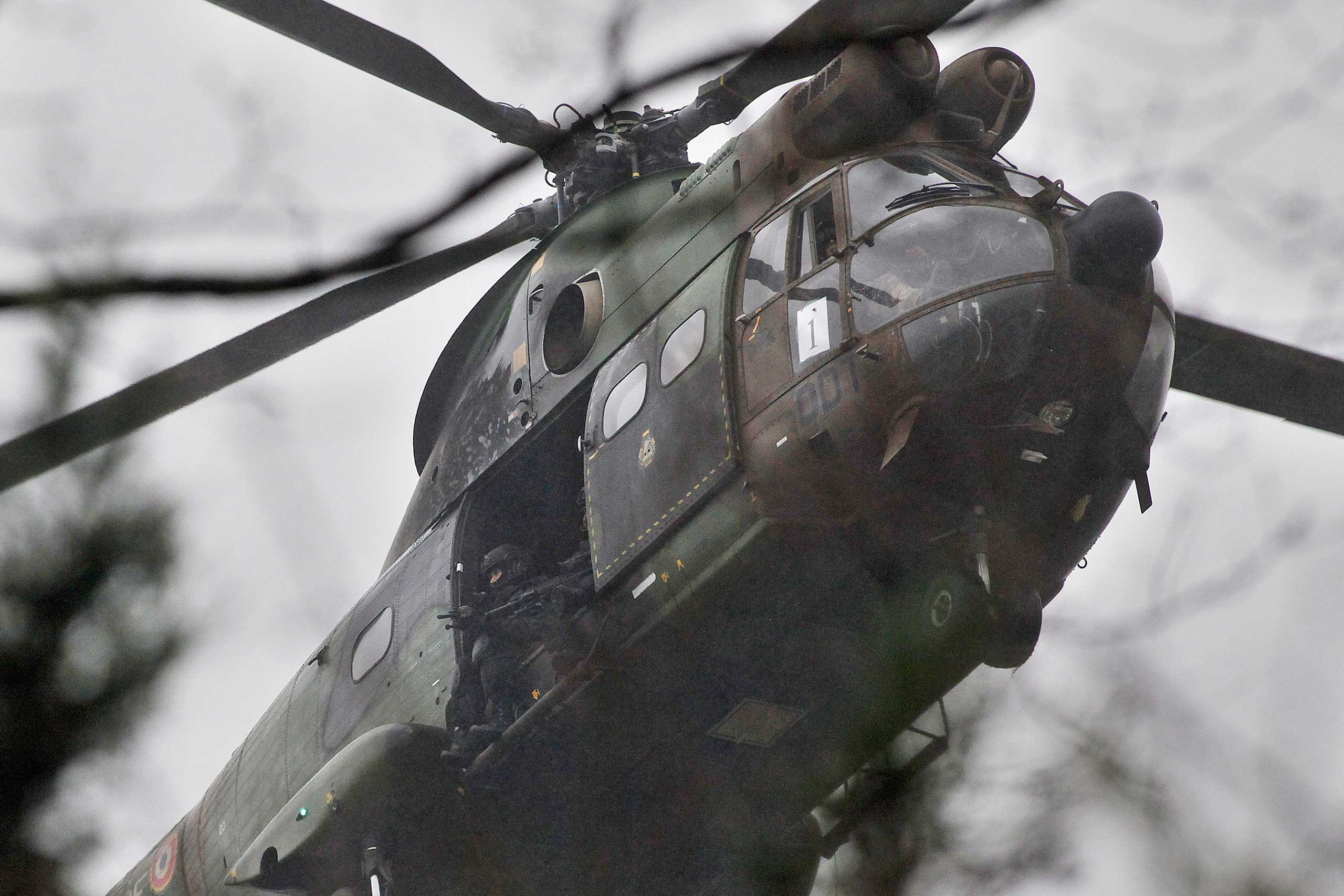Armed security forces fly overhead in a military helicopter  in Dammartin-en-Goele, northeast of Paris,  Jan. 9, 2015.