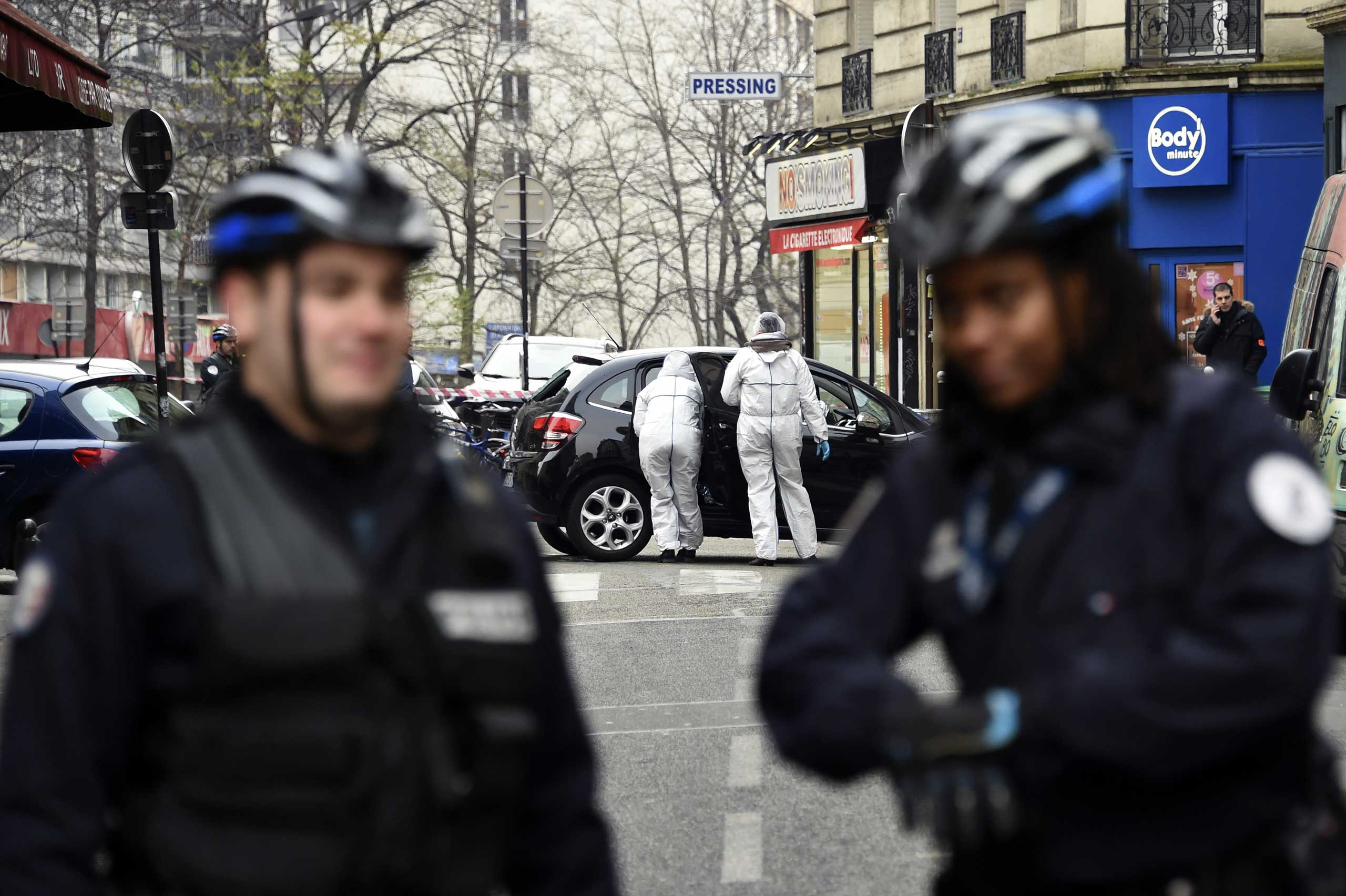 French police officers and forensic experts examine the car used by armed gunmen who stormed the Paris offices of satirical newspaper Charlie Hebdo on Jan. 7, 2015 in Paris.