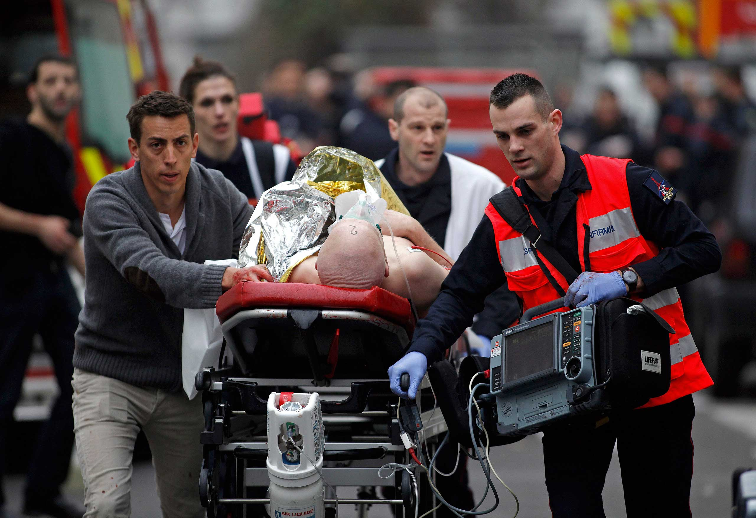 An injured person is evacuated outside the French satirical magazine Charlie Hebdo's office, in Paris, Jan. 7, 2015.