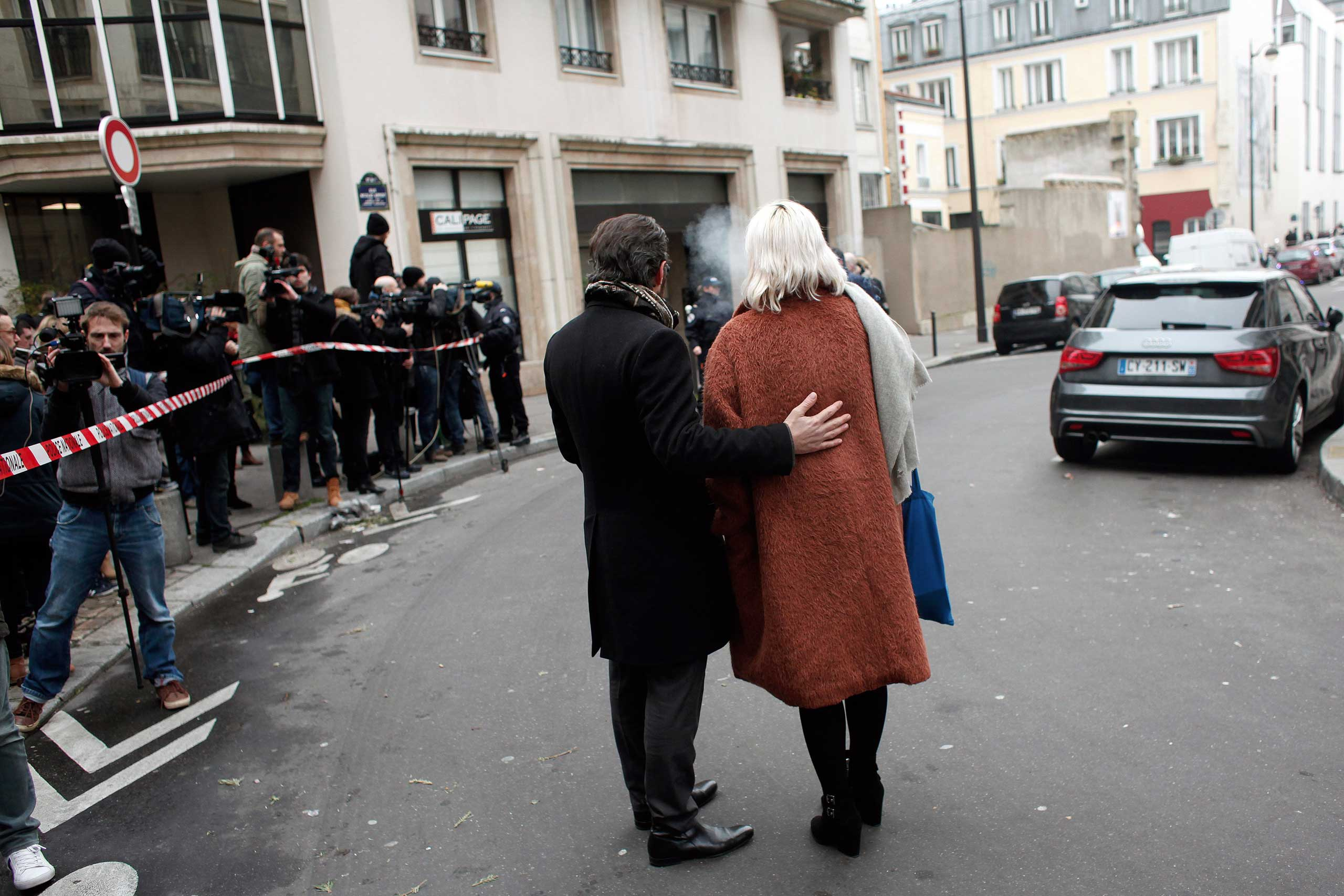 People stand outside the French satirical newspaper <i>Charlie Hebdo</i>'s office after a shooting, in Paris on Jan. 7, 2015