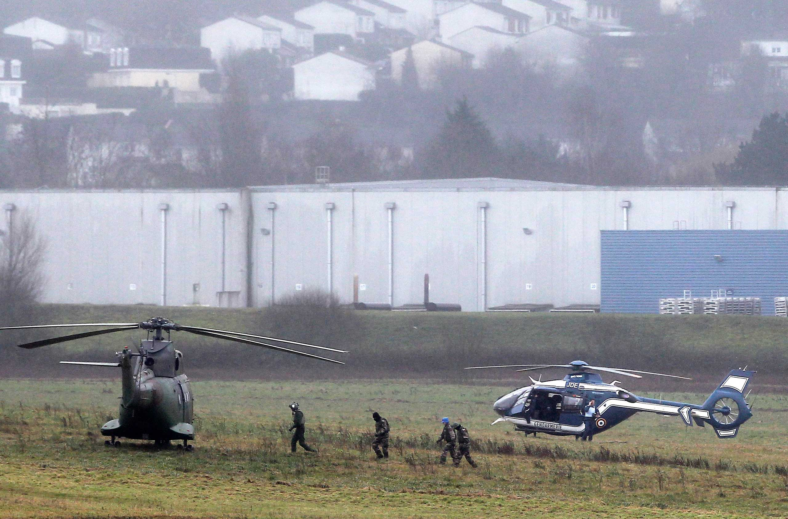 Police and army forces take positions in Dammartin-en-Goele, northeast Paris, as part of an operation to seize two heavily armed suspects, Jan. 9, 2015.