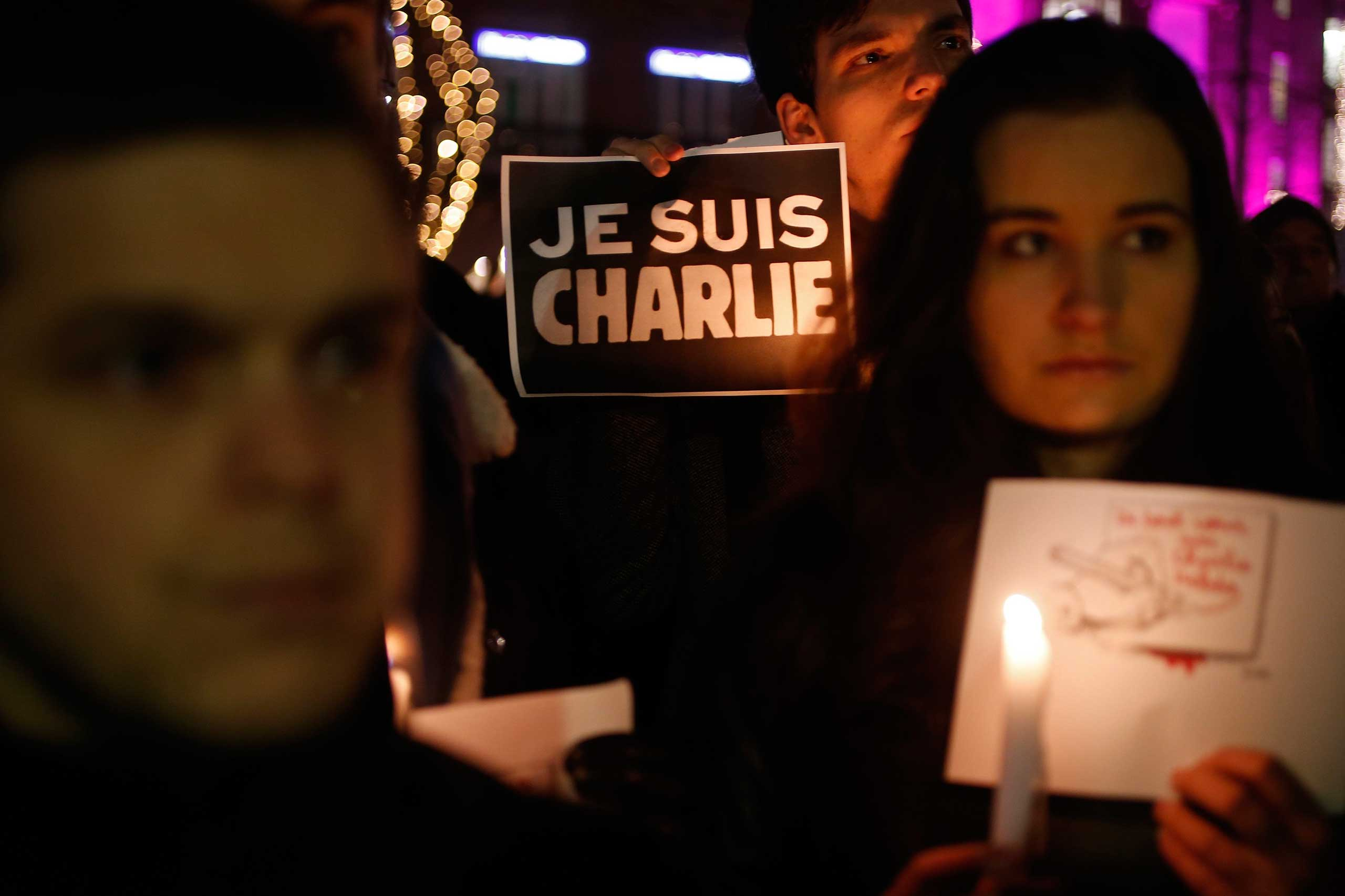 A person holds a candle next to a placard which reads  I am Charlie  to pay tribute during a gathering in Strasbourg on Jan. 7, 2015,