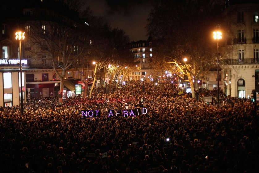 People gather to pay respect for the victims of a terror attack against a satirical newspaper, in Paris, Jan. 7, 2015.