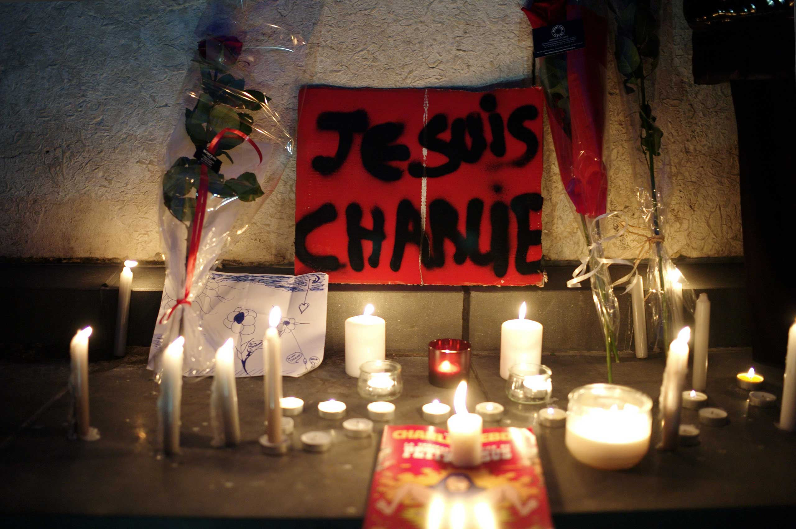 "A banner reading ""I am Charlie"" is displayed with candles during a gathering to pay respect for the victims of a terror attack against a satirical newspaper, in Paris, Jan. 7, 2015."