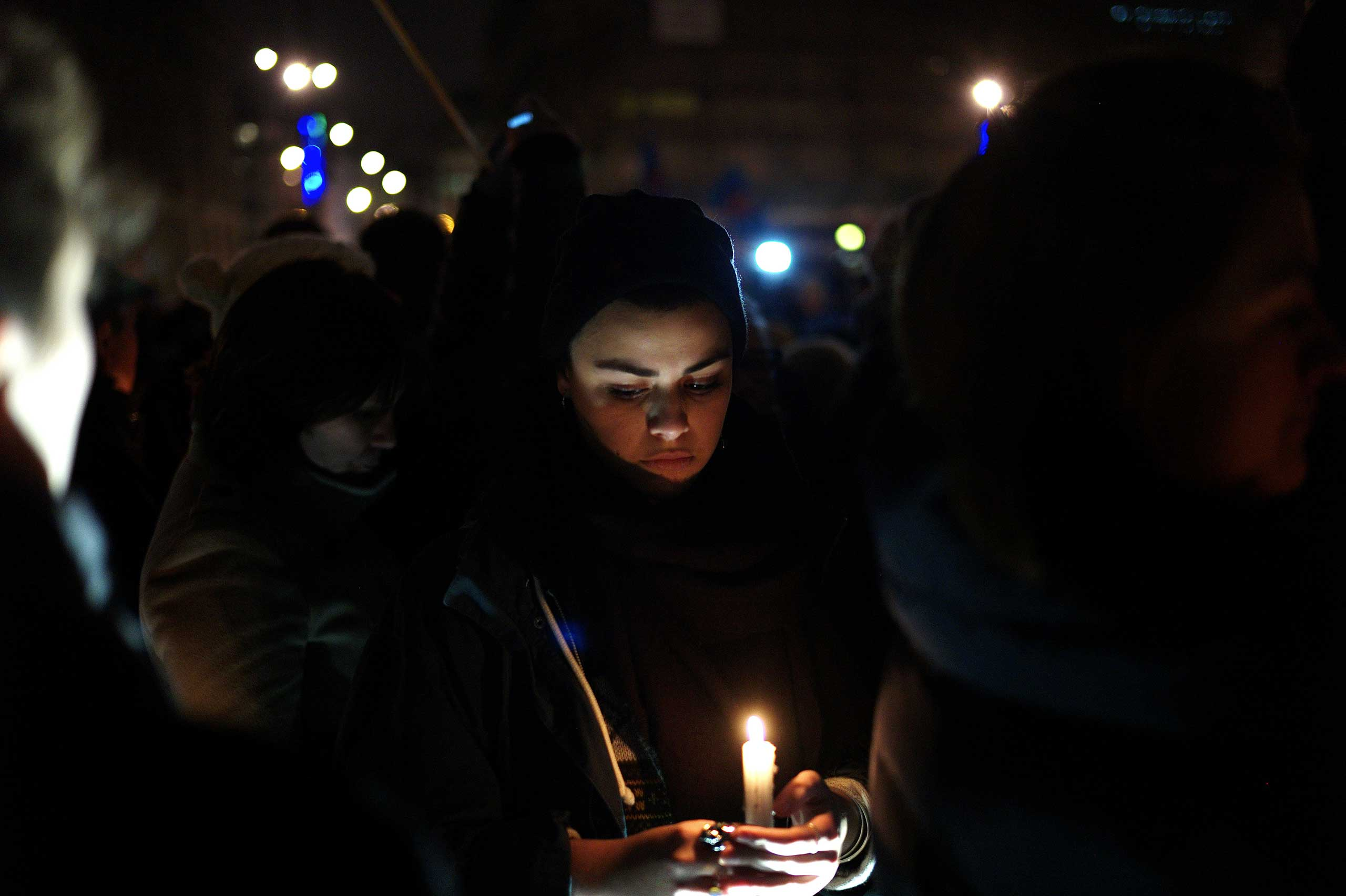 A woman holds a candle during a gathering to pay respect for the victims of a terror attack against a satirical newspaper, in Paris, Jan. 7, 2015.
