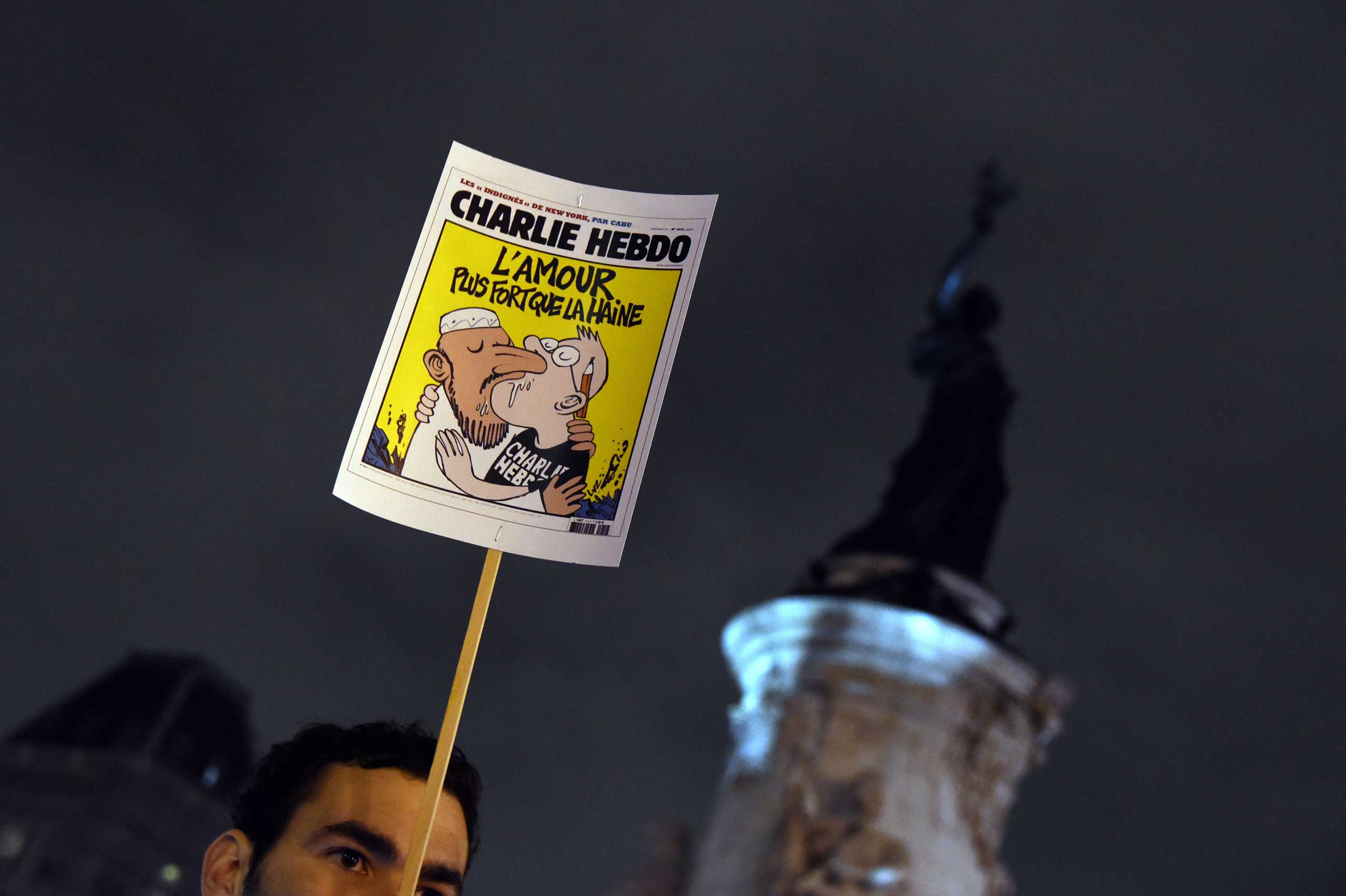 "A man holds a placard with a Charlie Hebdo front page reading ""Love is stronger than hate"" during a gathering at the Place de la Republique in Paris, on Jan. 7, 2015."