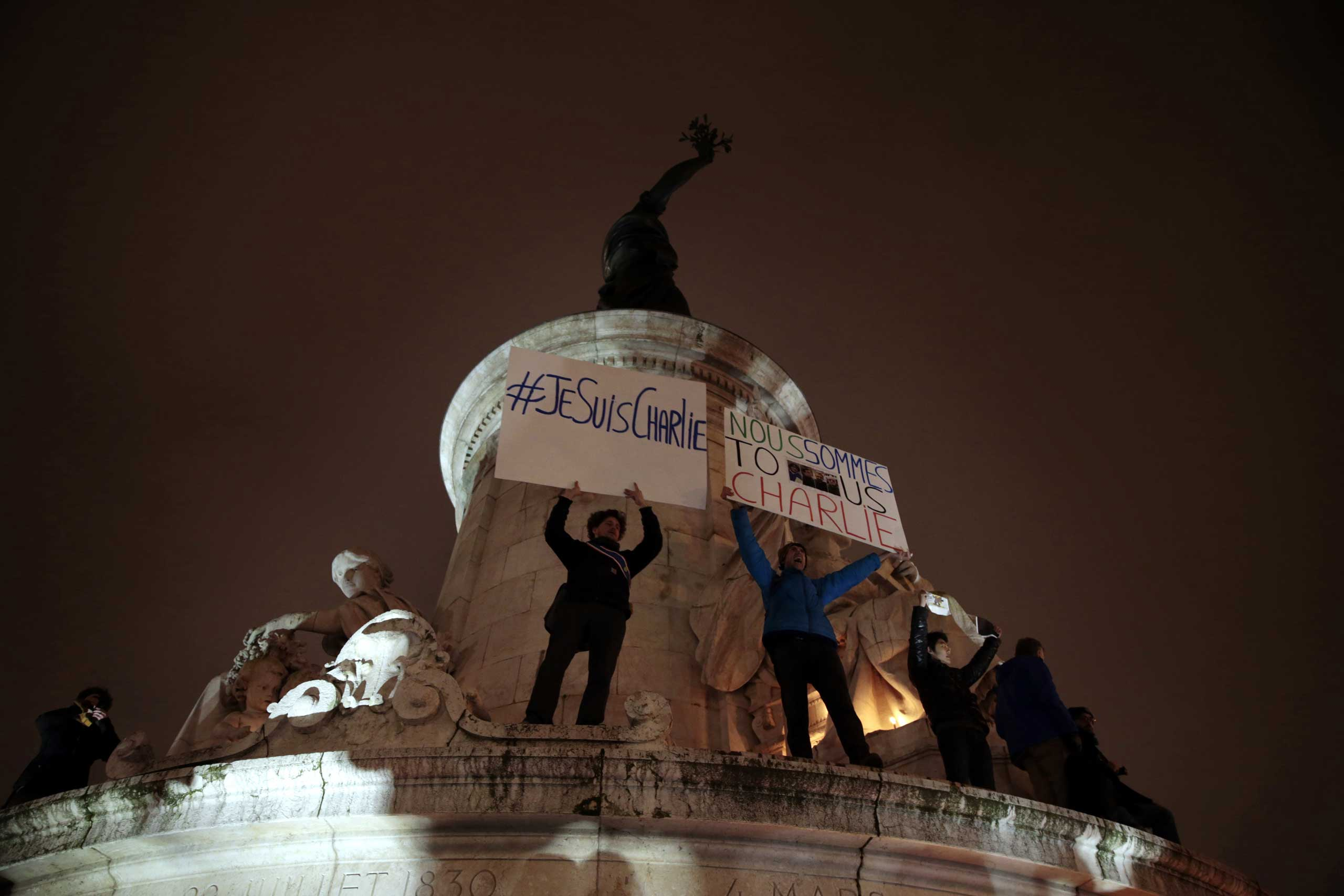 "People hold placards reading in French ""I am Charlie"" and ""We are all Charlie"" during a gathering at the Place de la Republique in Paris, on Jan. 7, 2015."