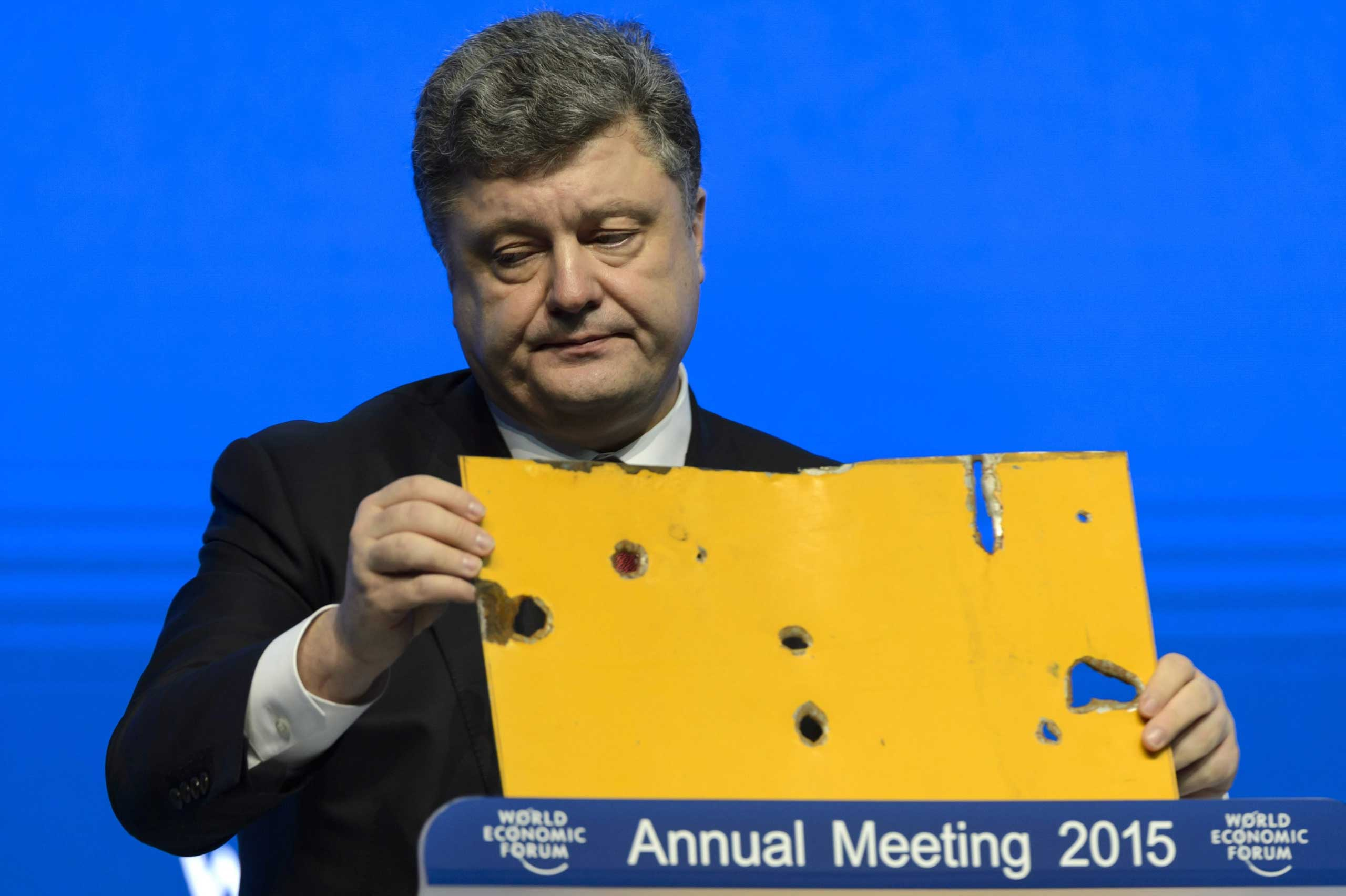 The president of Ukraine Petro Poroshenko speaks with a piece of a damaged passenger bus hit by a shell that killed twelve passengers and injured 13 others at a Ukrainian military checkpoint near the town of Volnovakha, during a panel session on the first day of the 45th Annual Meeting of the World Economic Forum, WEF, in Davos, Jan. 21, 2015.