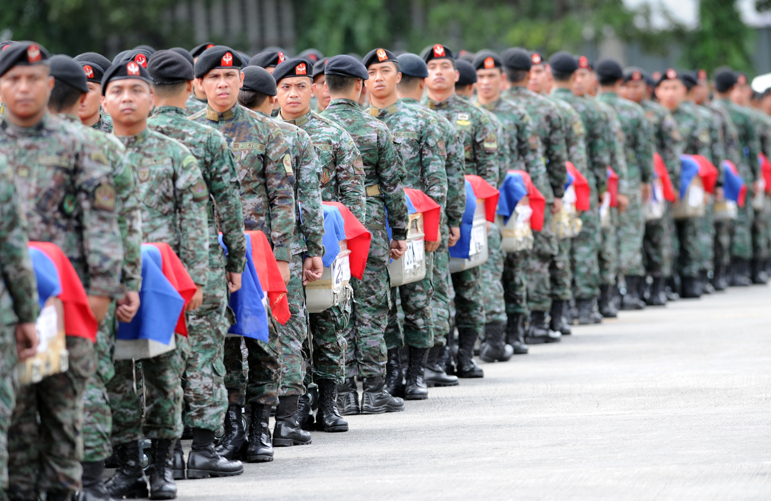 Philippine police commandos stand at attention next to the flag-draped coffins of their slain comrades shortly after arriving at a military base in Manila on Jan. 29, 2015