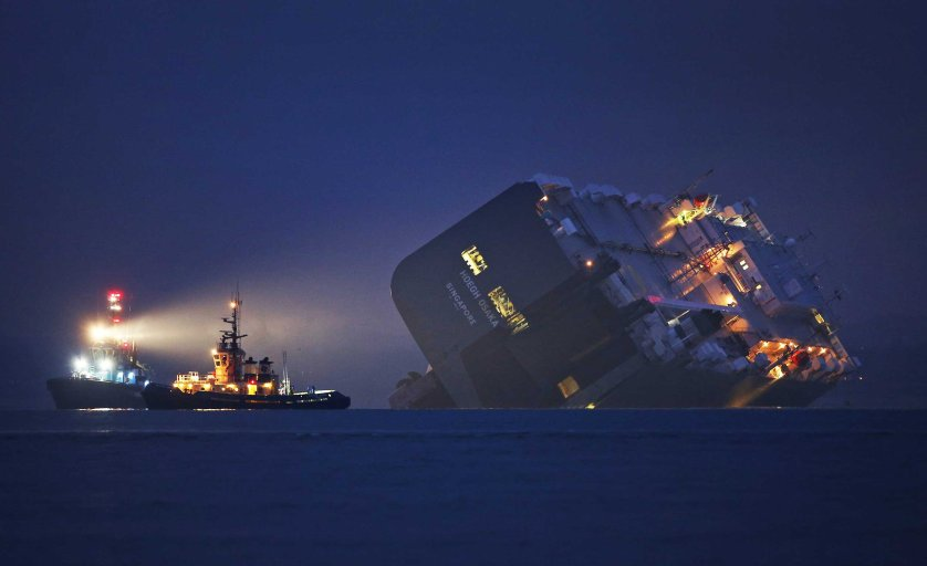 Jan 4. 2015. A salvage tug lights the hull of the stricken Hoegh Osaka cargo ship after it ran aground on a sand bank Cowes, England.