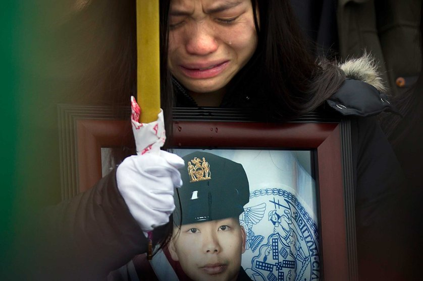 Jan. 4, 2015. Tears shed by widow Pei Xia Chen fall onto the frame of a portrait of her slain husband, New York Police Department officer Wenjian Liu, as his casket departs his funeral in New York.