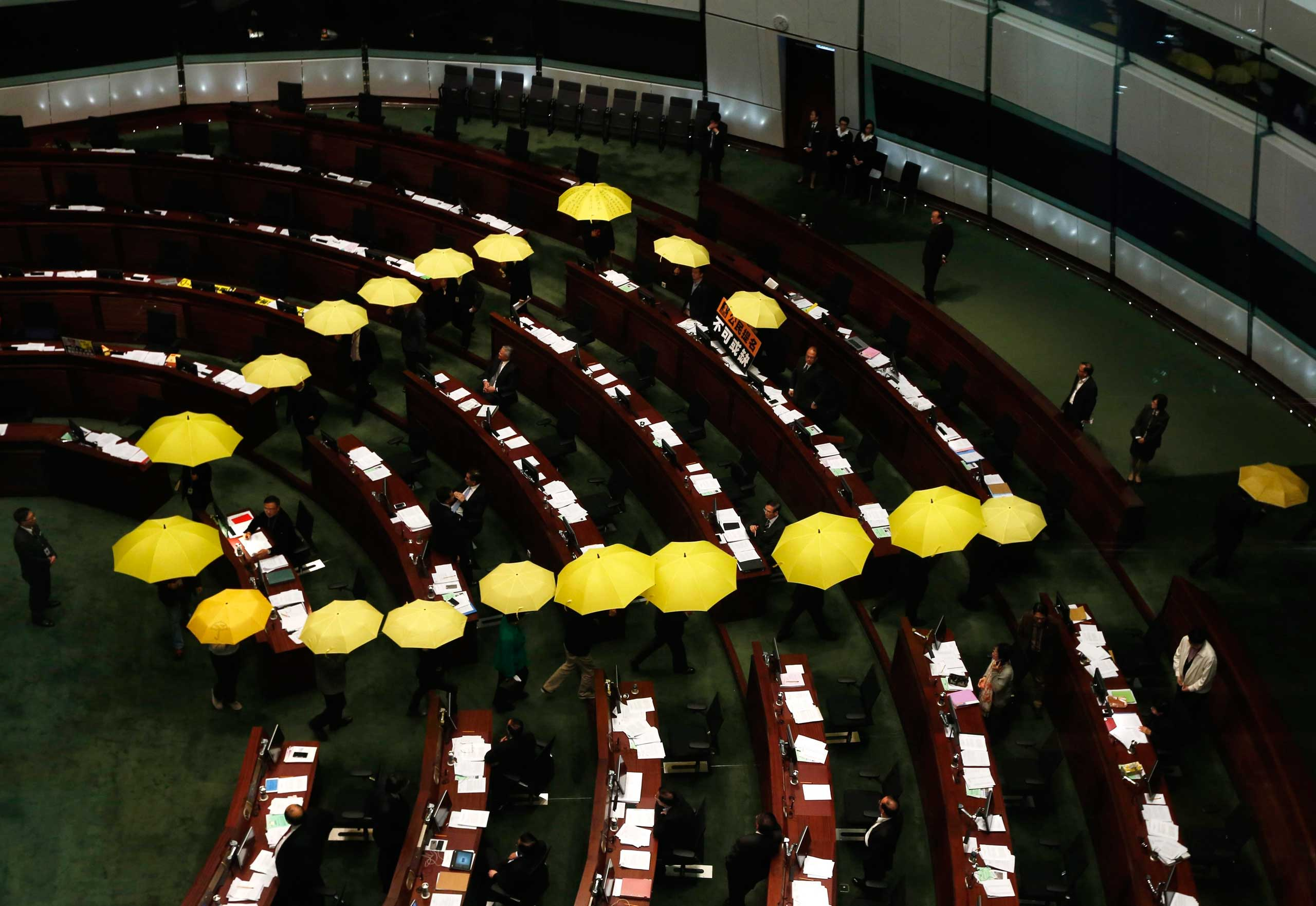 Jan. 7, 2015. Pro-democracy lawmakers carrying yellow umbrellas, symbols for the Occupy Central movement, leave in the middle of a Legislative Council meeting as a gesture to boycott the government in Hong Kong.
