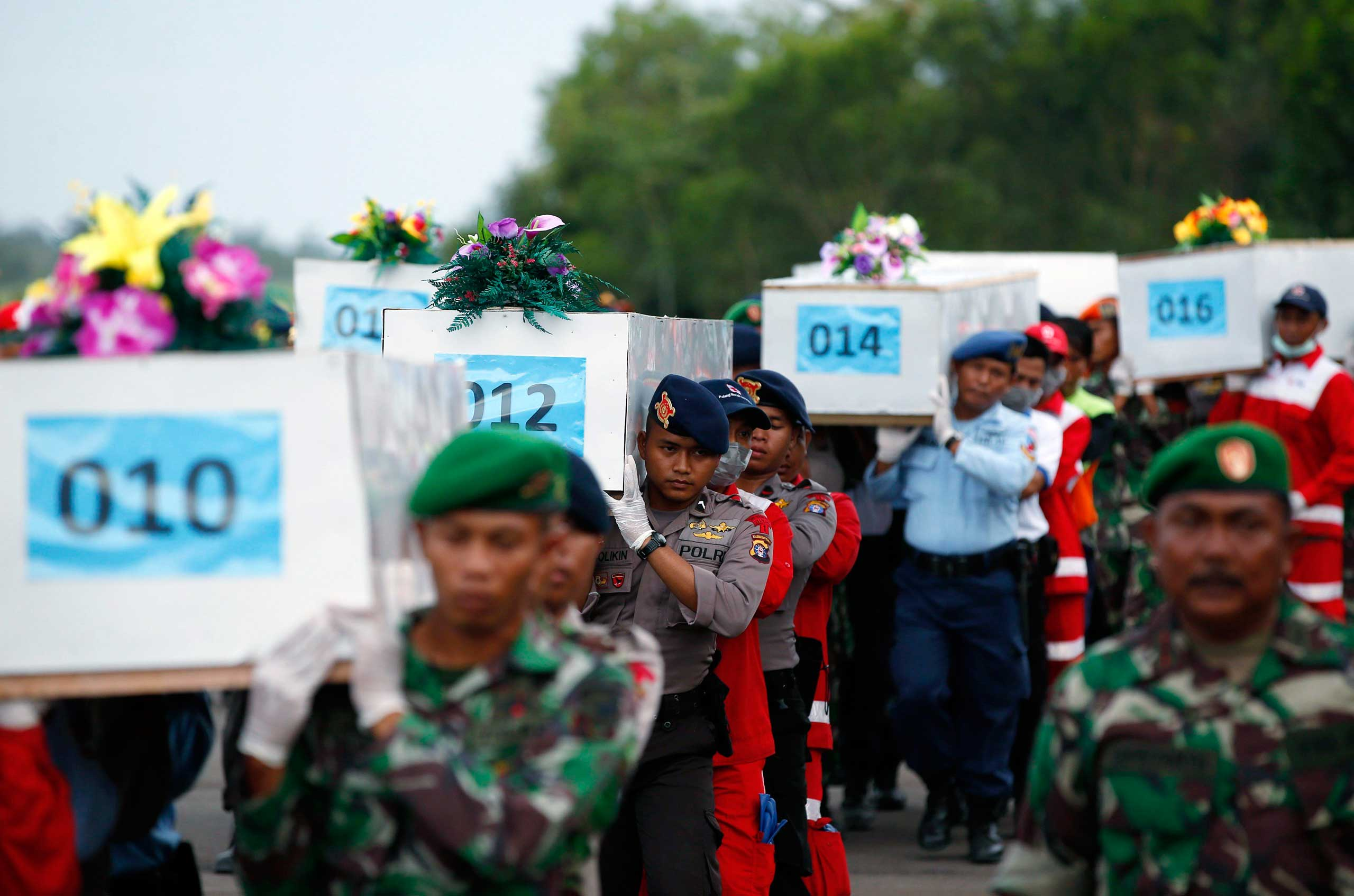 Jan. 2, 2015. Caskets containing the remains of AirAsia QZ8501 passengers recovered from the sea are carried to a military transport plane before being transported to Surabaya, Indonesia.