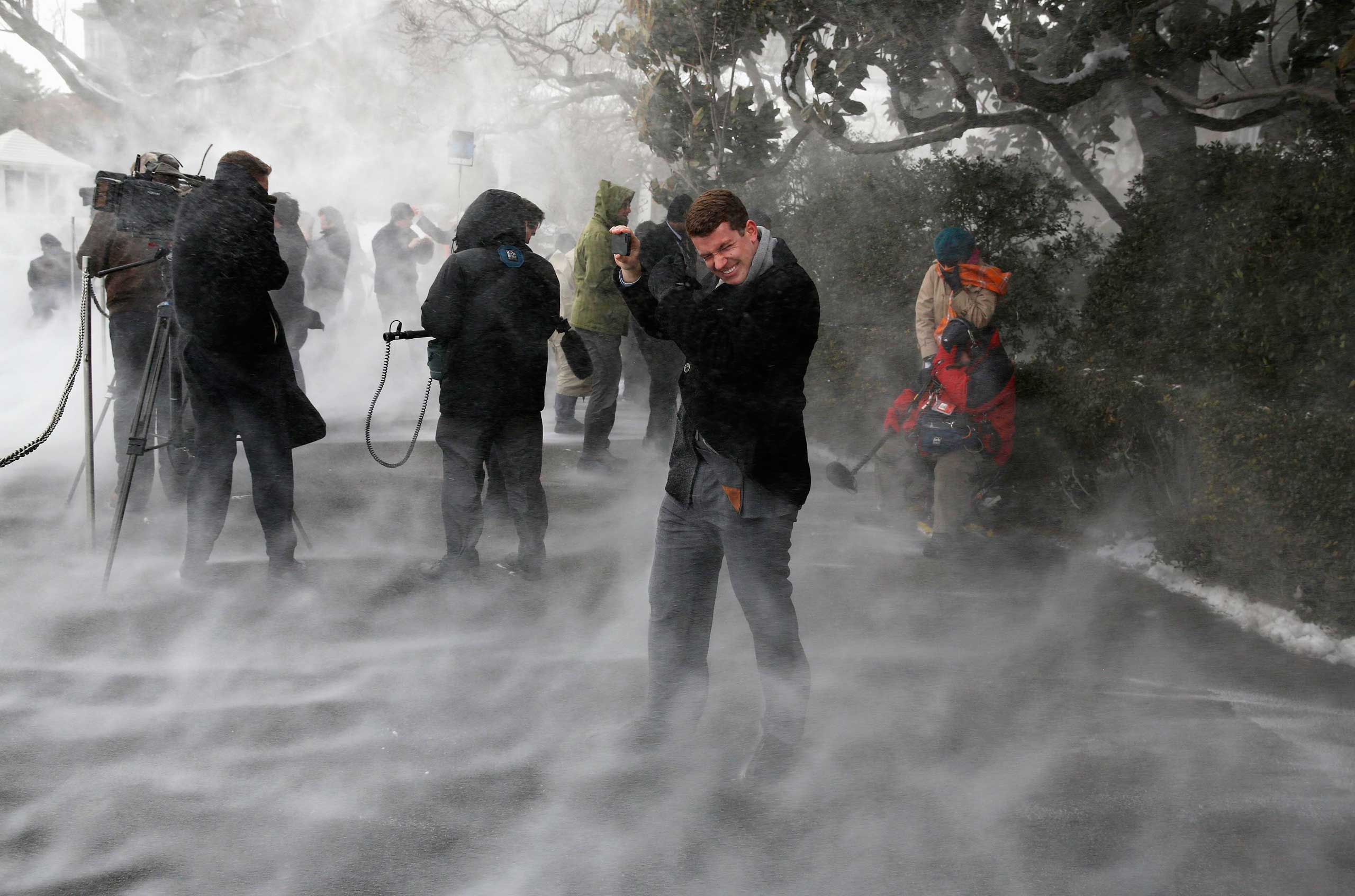 Jan. 7, 2015. Members of the press, including NBC's Evan Dixon, face the blowing snow caused by Marine One as it landed on the South Lawn before picking up U.S. President Barack Obama at the White House in Washington, D.C.
