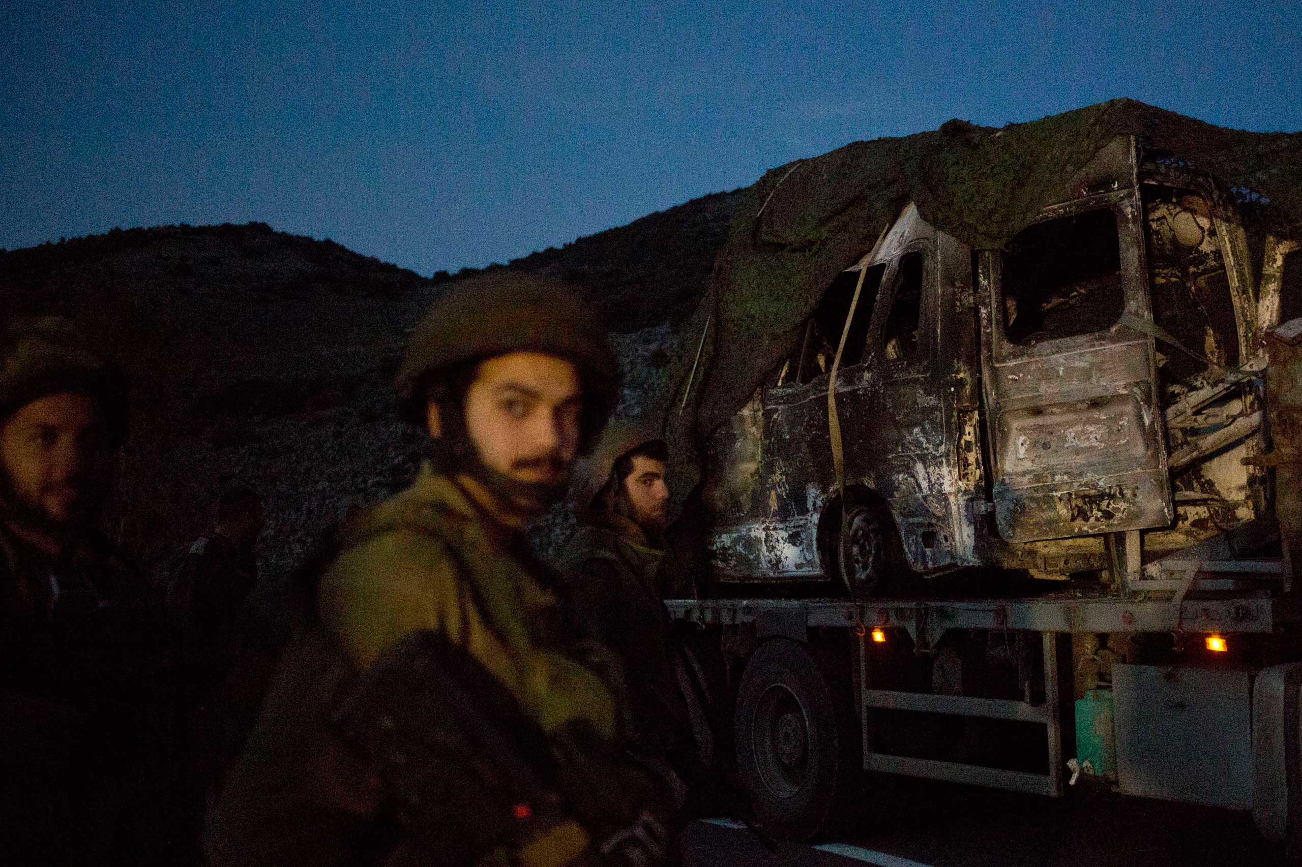 Jan. 28, 2015. Israeli soldiers watch as a truck carries the military vehicle that was hit by a missile fired by Hezbollah on the Israel-Lebanon border. The event killed two soldiers in an apparent retaliation for a deadly airstrike attributed to Israel that killed six Hezbollah fighters in Syria earlier this month.