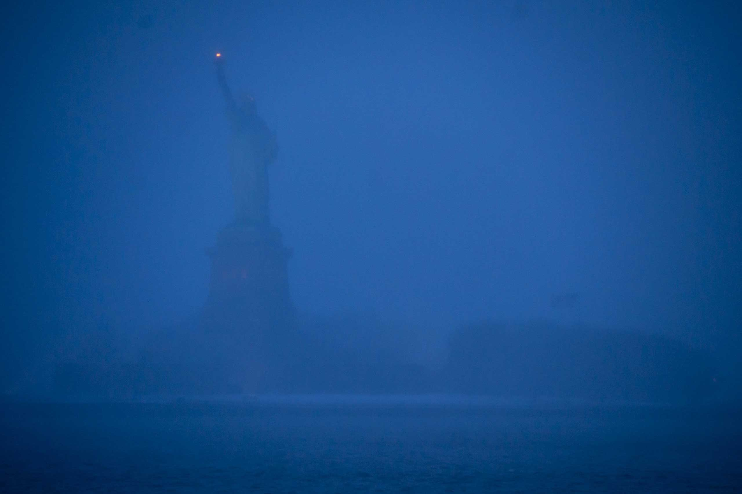 Jan. 26, 2015. The Statue of Liberty is seen faintly through heavy snow in New York. Millions of people from New Jersey to Maine left work early, rushed off roads and took shelter as a snowstorm bore down on the region.