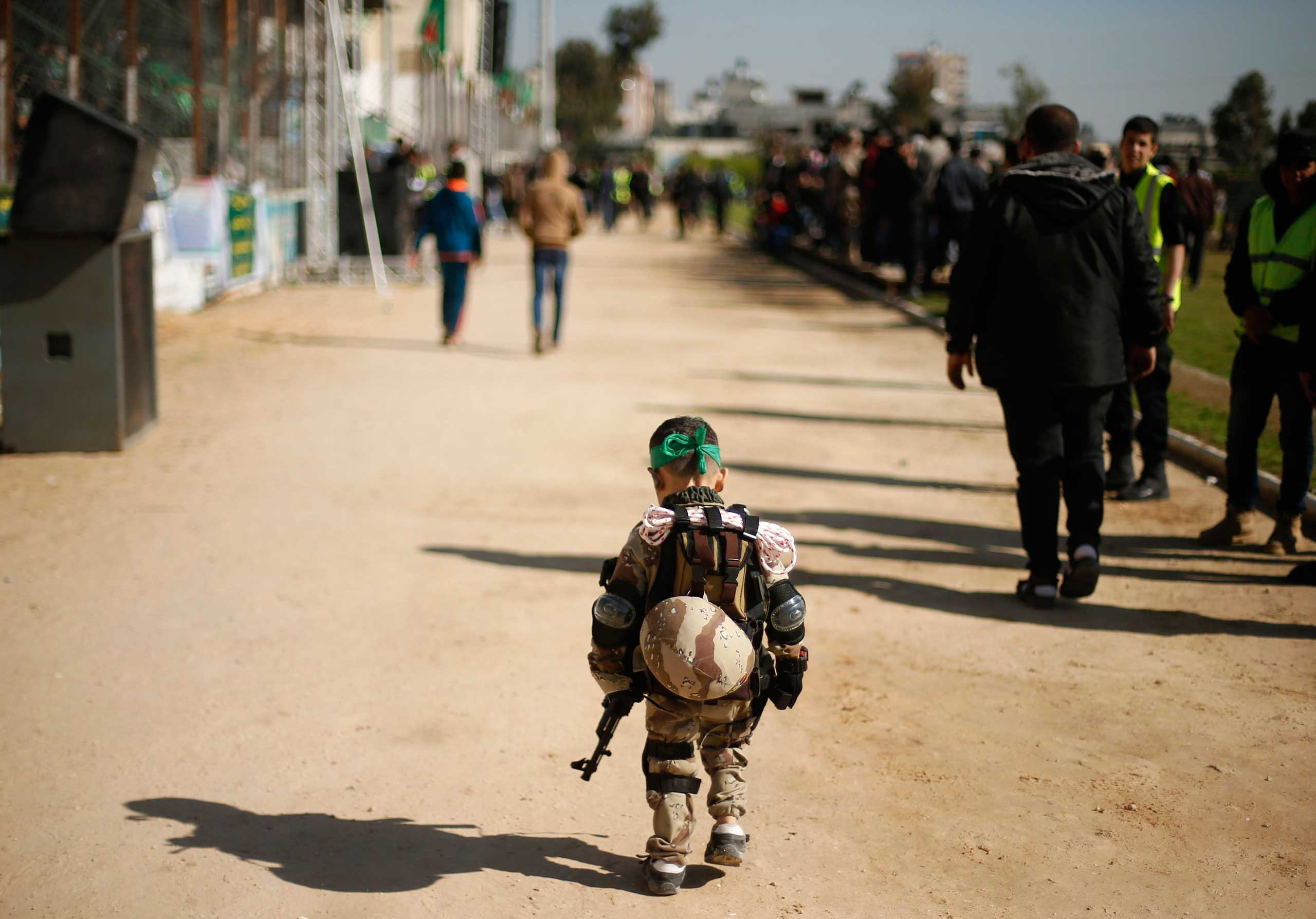 Jan. 29, 2015. A Palestinian boy wearing a military costume arrives at a military-style graduation ceremony for Palestinian youths who were trained at one of the Hamas-run liberation camps in Gaza. Some 17,000 youths graduated from these camps that aim to prepare them to confront Israeli attacks.
