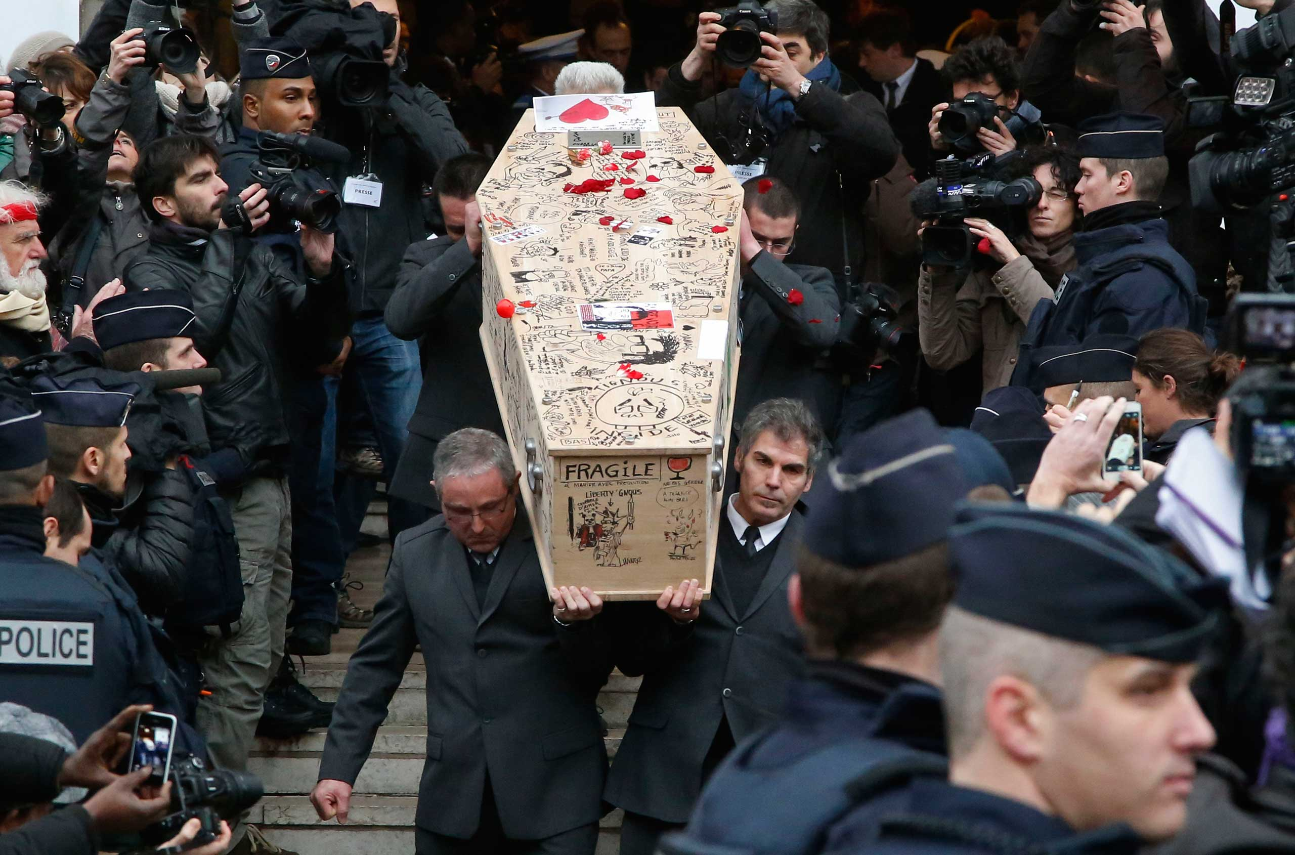 Jan. 15, 2015. Pallbearers carry the casket of Charlie Hebdo cartoonist Bernard Verlhac, known as Tignous, decorated by friends and colleagues of the satirical newspaper Charlie Hebdo, at the city hall of Montreuil, outside east of Paris.