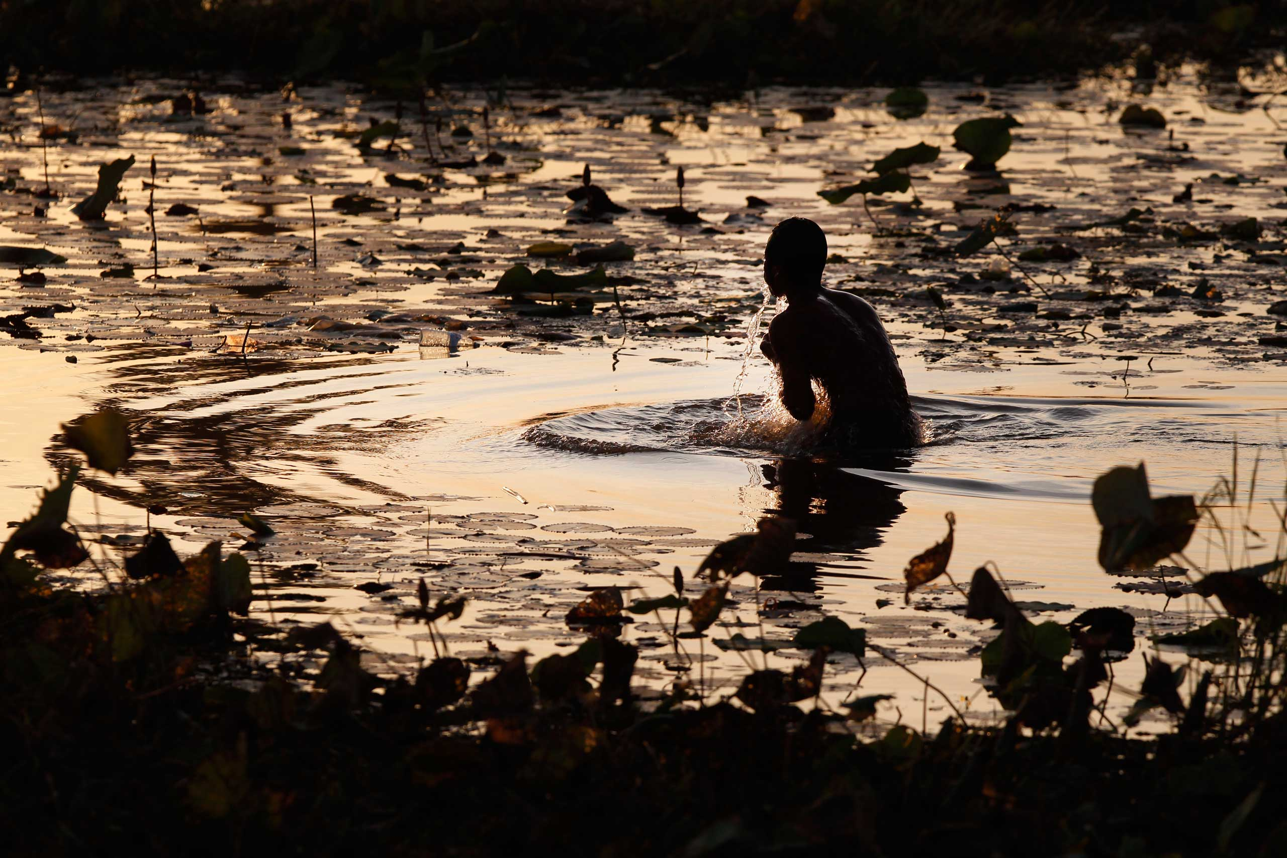 Jan. 11, 2015. A man takes his evening bath in a pond at O-Treng village at the outskirt of Phnom Penh.