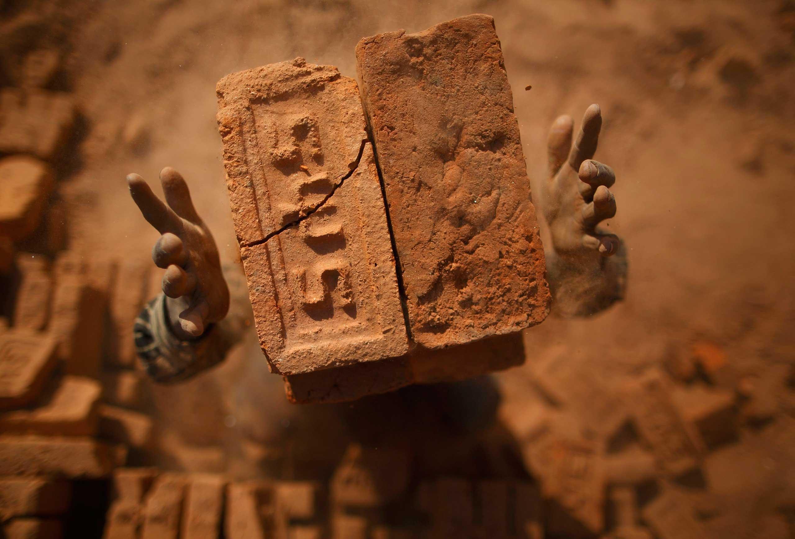Jan. 12, 2015. A worker stacks bricks on his head at a brick factory in Lalitpur, Nepal.