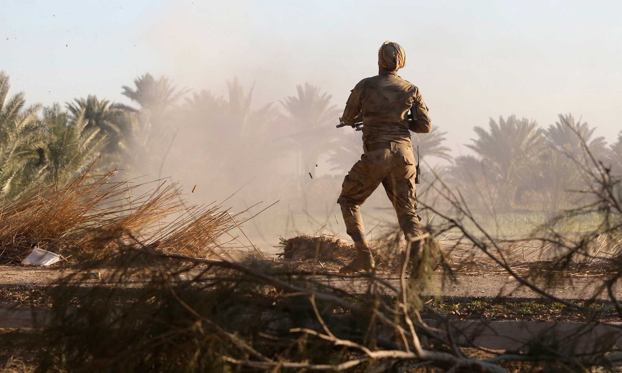 Jan. 12, 2015. An Iraqi Shi'ite fighter fires his weapon during fighting with Islamic State militants at Al-Nibai, north of Baghdad.