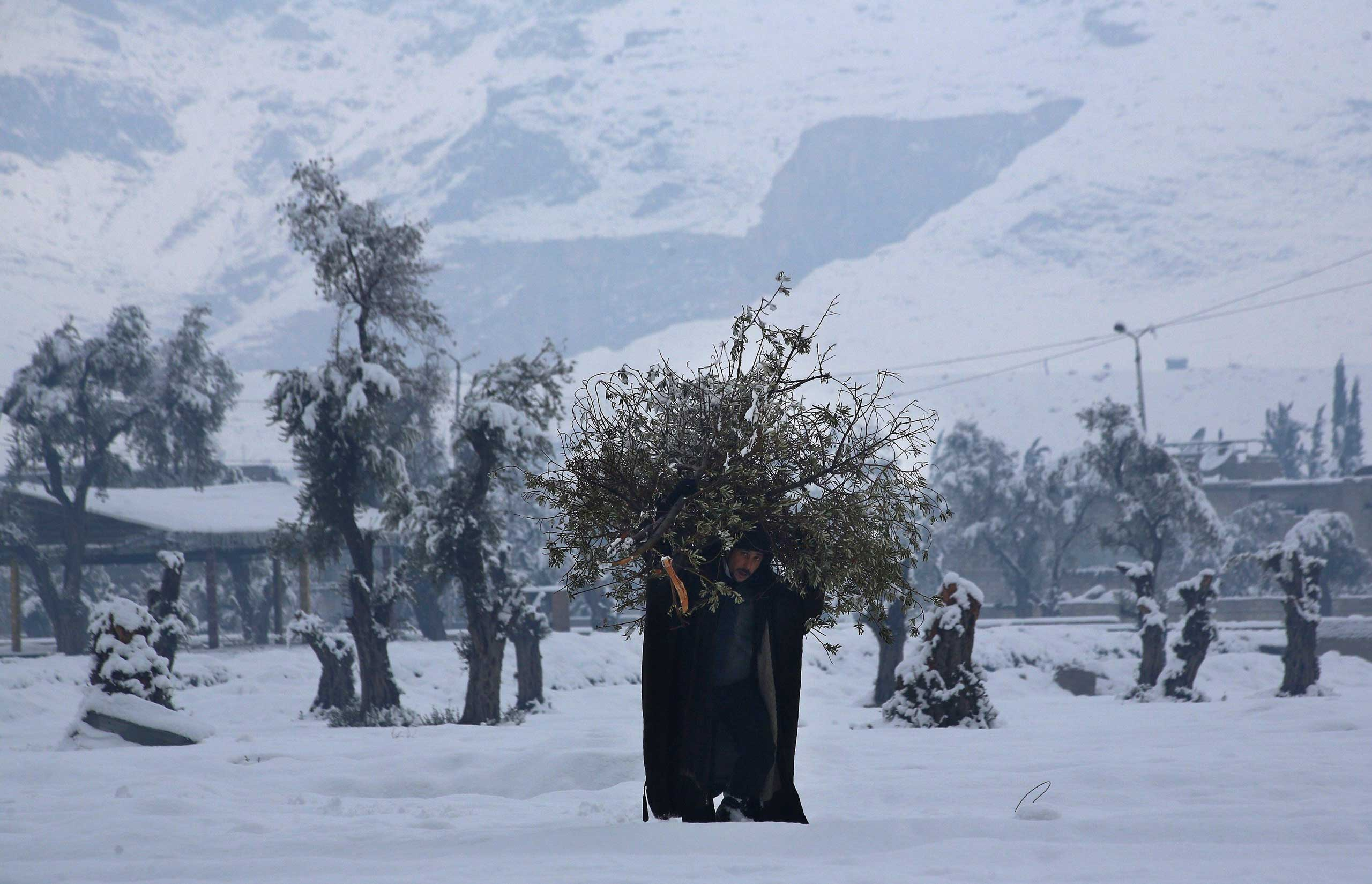 Jan. 11, 2015. A Syrian man carries wood for a fire in the rebel-held city of Douma. Syria's recent stretch of icy weather has taken a toll on people                               living in cities like rebel-held Douma, but but it has also stymied violence.
